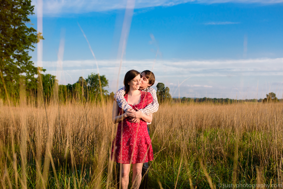 Beautiful engagement shots with couple kissing in field.