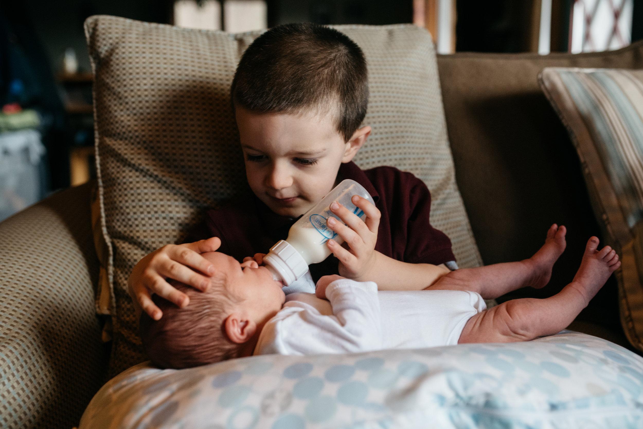 Brother feeding newborn brother lifestyle photographs