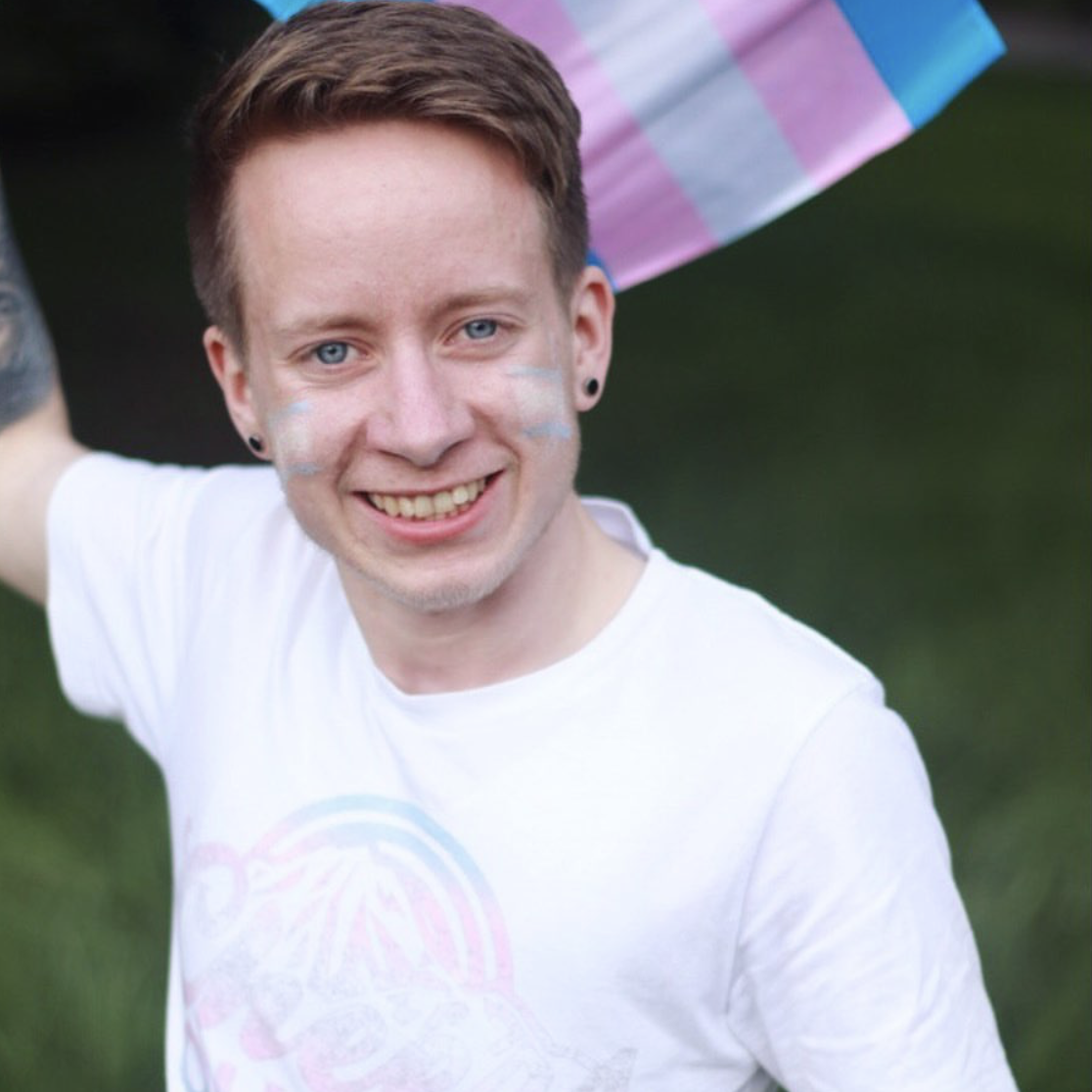 Jonas (he/him) - Making our Limited Edition Trans Pride Cheers Queers Tee look damn fine.