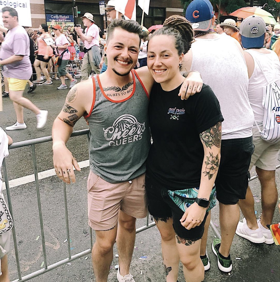 Chris (he/him) & Courtney (she/her) - Chris Flavnting our Cheers Queers Tank & Courtney in our Limited Edition Trans Pride Gal Pals tee!