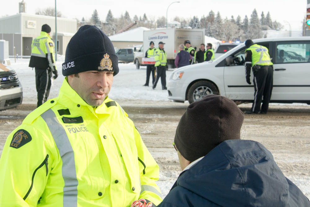 Constable Devon Firth from Picture Butte RCMP offers a candy cane to a pedestrian.