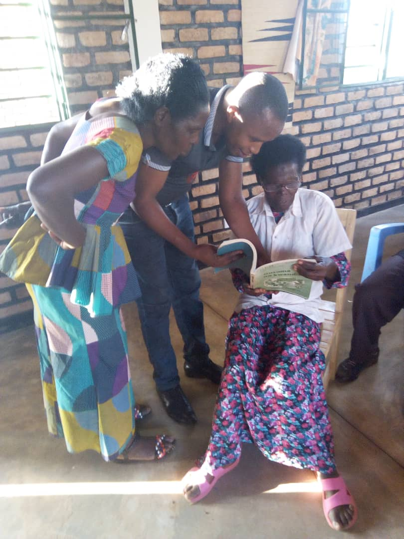 REAP literacy specialist and a community literacy teacher help a 72 year old read with new glasses.JPG