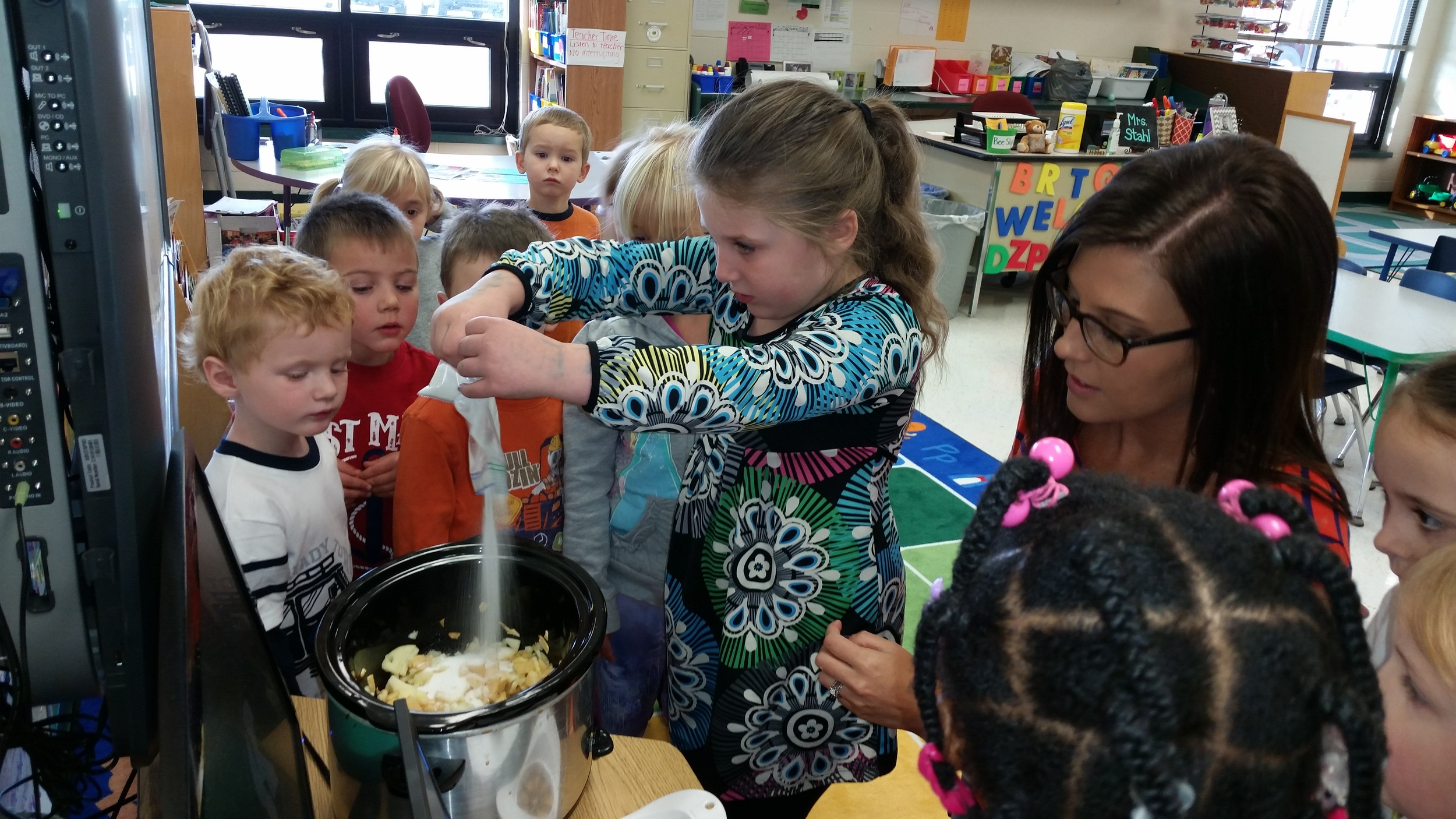 Adding sugar to our homemade applesauce!