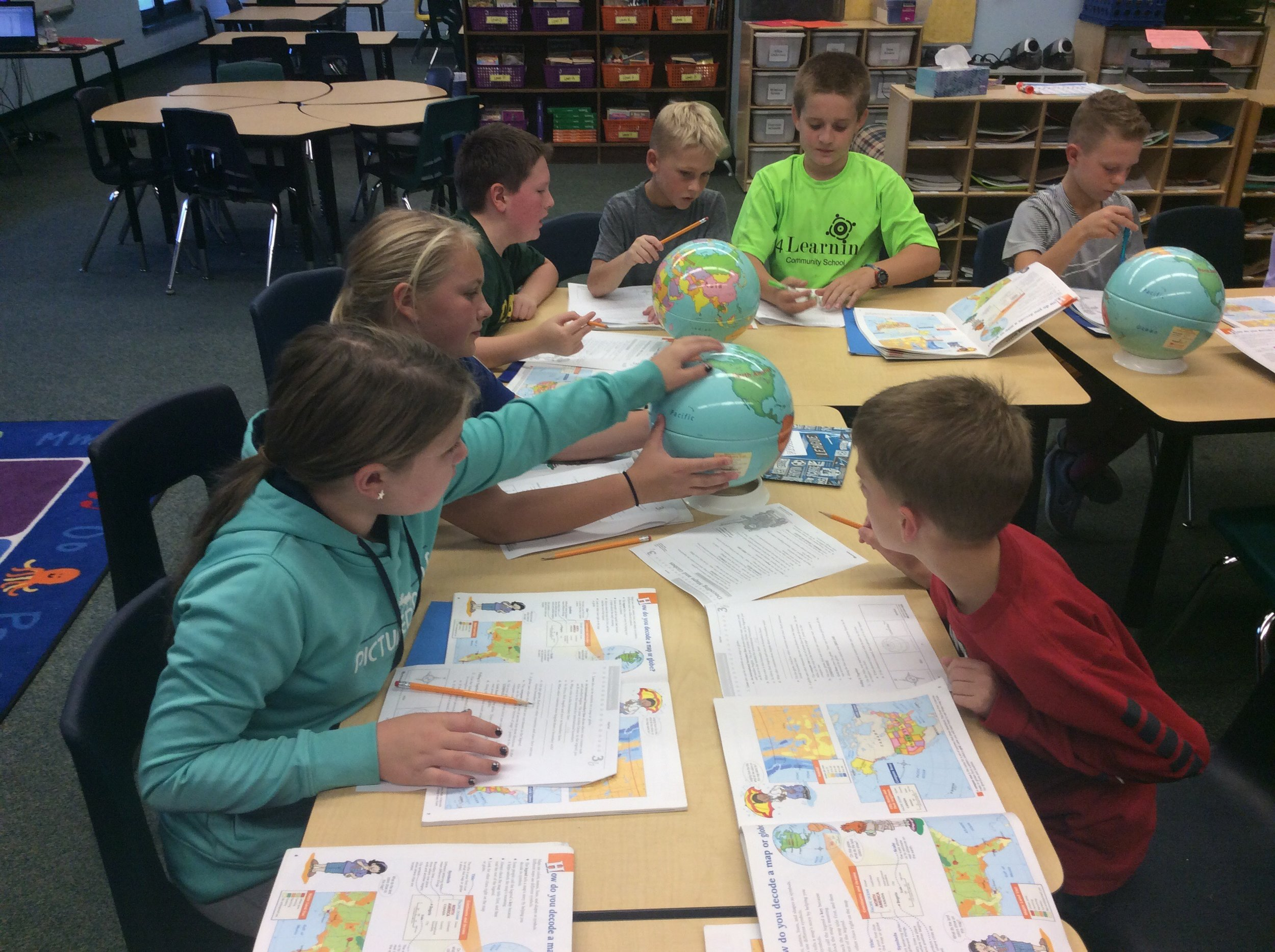 Students work as a small group to identify features found on globes and maps.