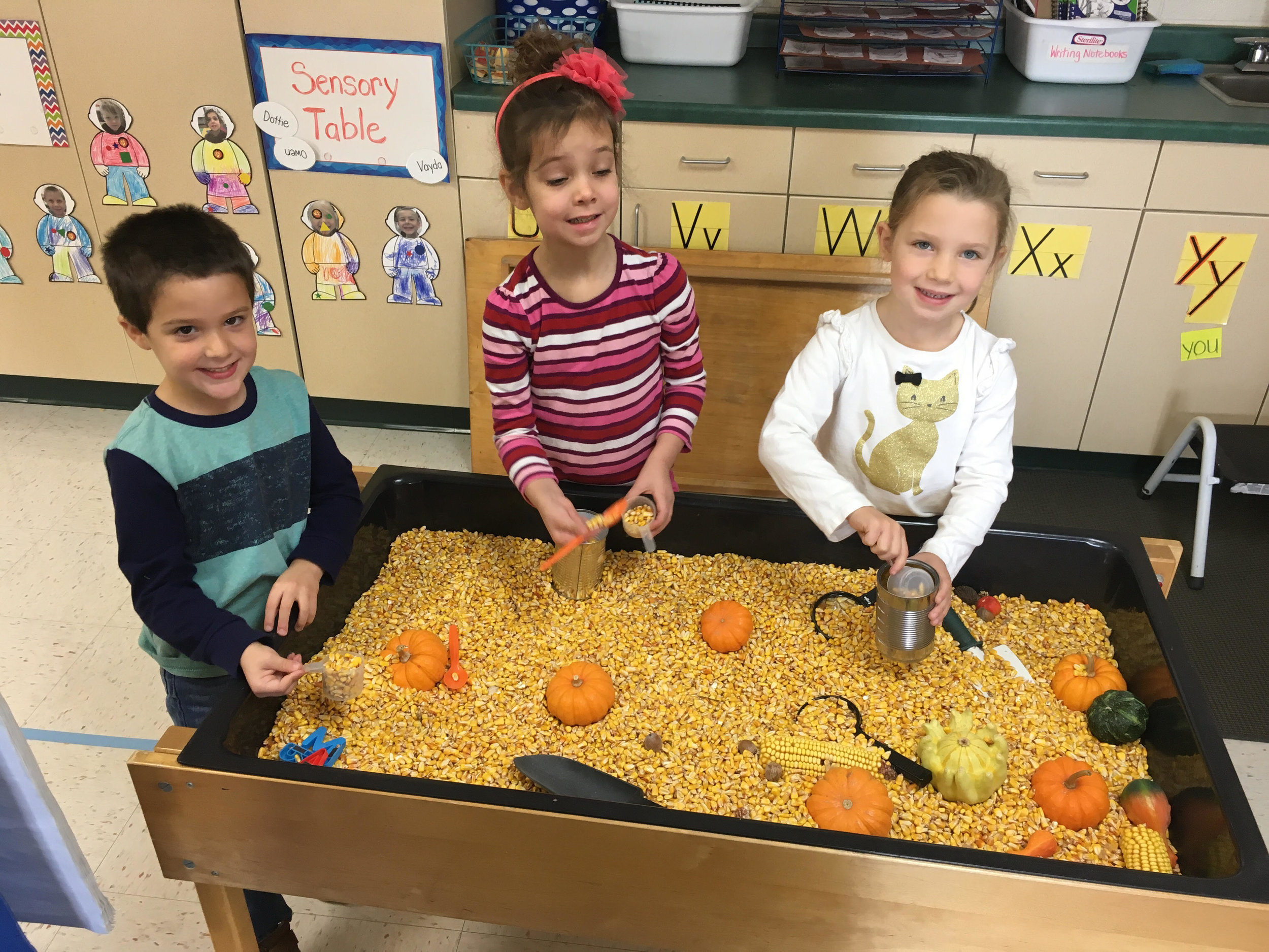 playing with corn in the sensory table
