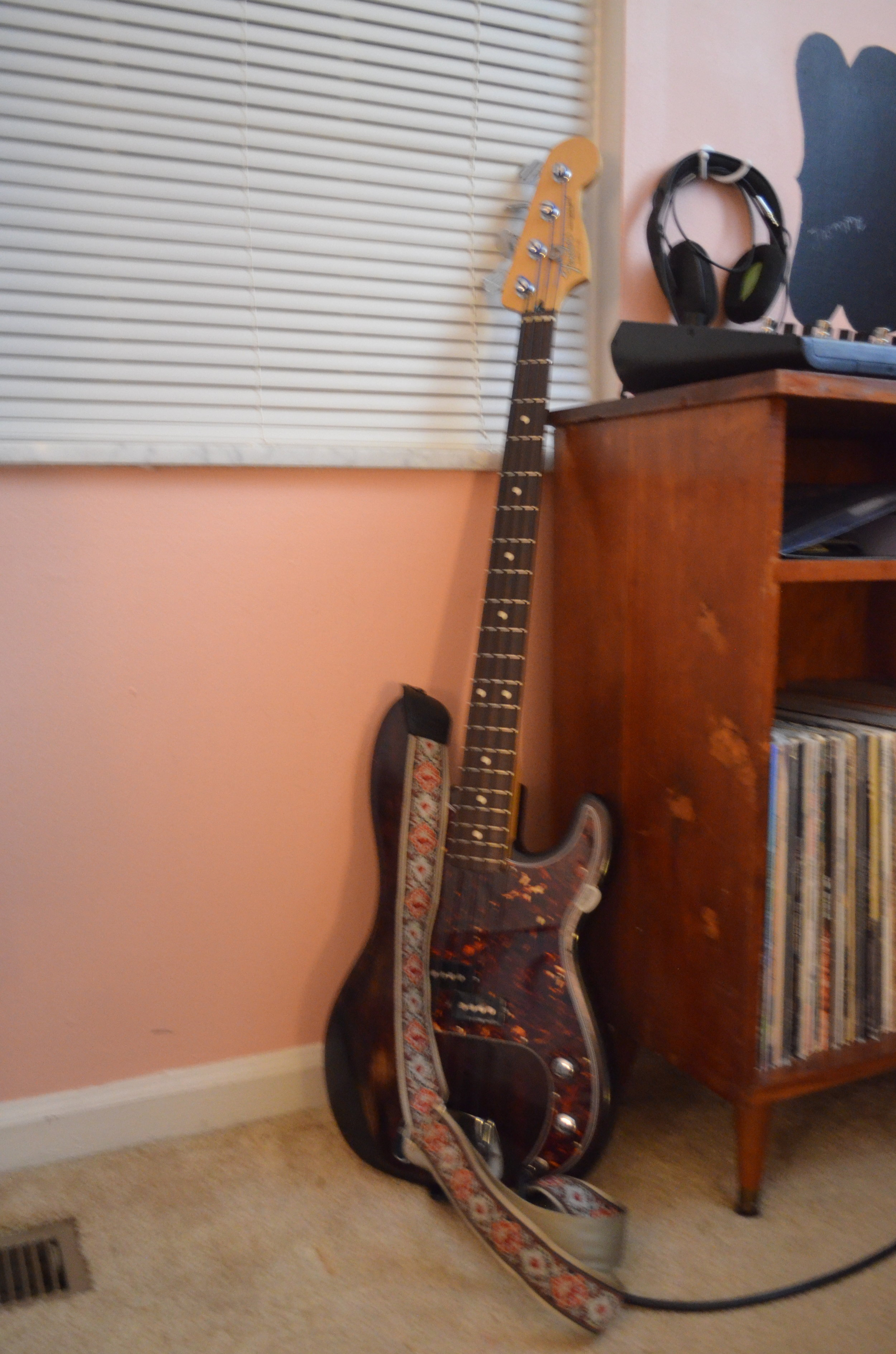 """This is my Fender Precision Bass - Bass guitar is a significant part of """"Little Flock."""" When I called it quits on our full band in 2016, I started playing bass more than guitar. Although I still have a long way to go, and I lack certain qualities of 'true' bassists, I feel confident behind the instrument. I consider bass the key instrument behind many of the songs on the album. Utilizing the bass guitar (or bass synth) to serve a song's structure has been one of the biggest steps forward I've taken as a musician in the last couple years.The neck on this bass is from 1994, I think? Mexican made. The body is also Mexican, but it's from a different year. It came with a Seymour Duncan Basslines pickup in it, and I upgraded the bridge at some point. I also prefer tape-wound strings for the warm, smooth tone they provide. It's not really worth much attention, but it does what I want it to do, and it feels good under my fingers."""