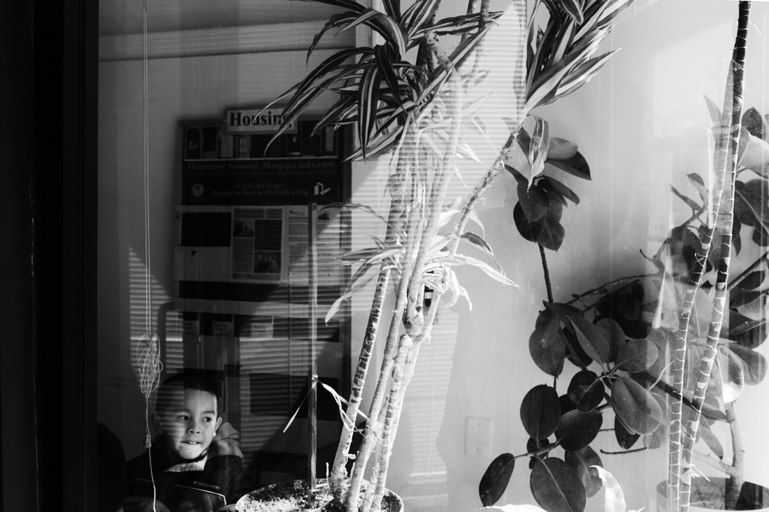 A young boy is looking outside the window at the Chinese Mutual Aid Association in Uptown. Mutual Aid Associations are vital to assists refugees, immigrants and people from all socioeconomic and ethnic backgrounds with social services like adult education, citizenship and immigration, in-home services, employment services, youth programs and much more.