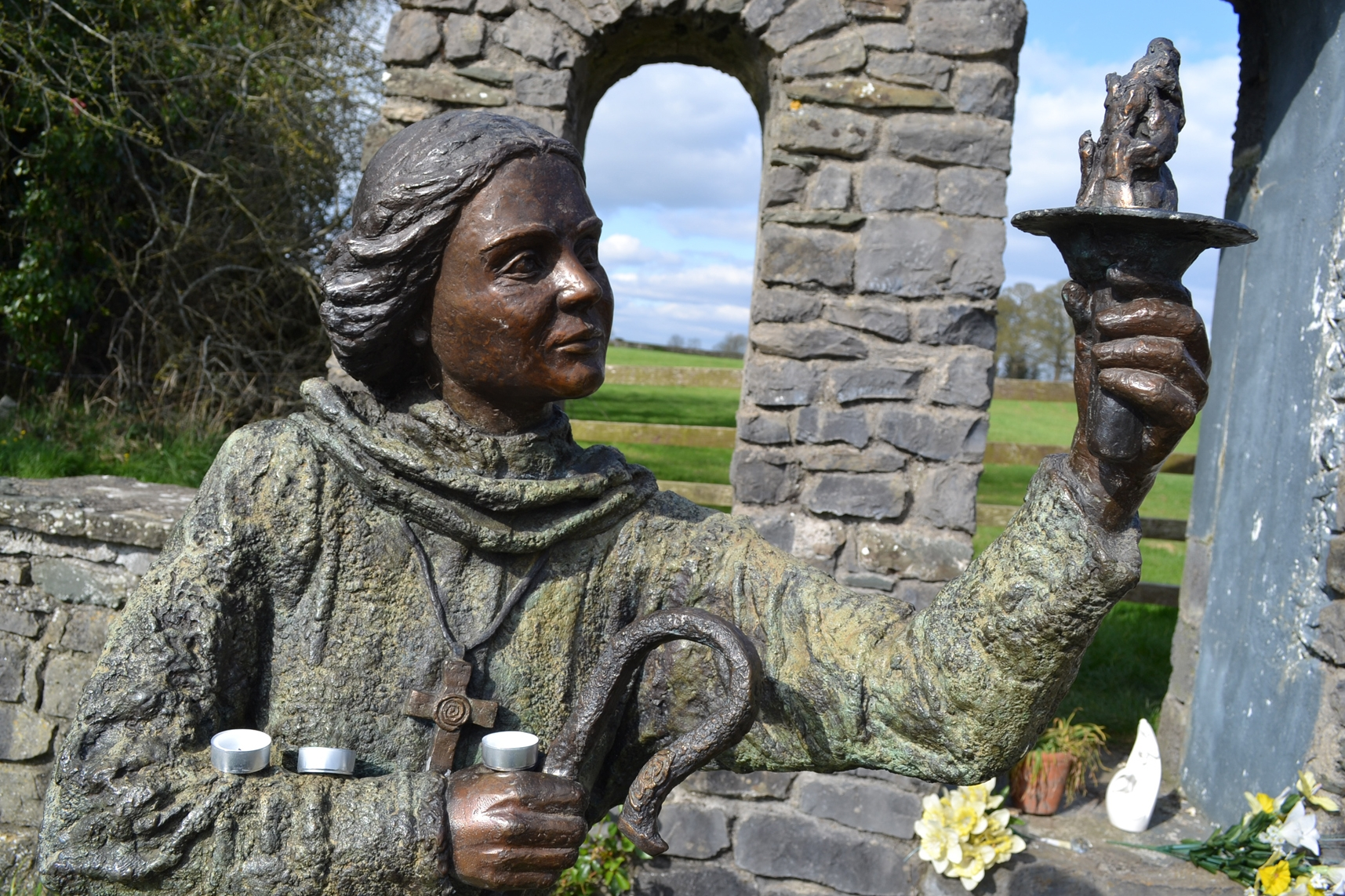 The statue of St Brigid (also known as St Bride) at St Brigid's Well, Kildare, Ireland. She is depicted holding a flame to represent the eternal flame that burned at the heart of the mixed gender abbey she built in the fifth century.