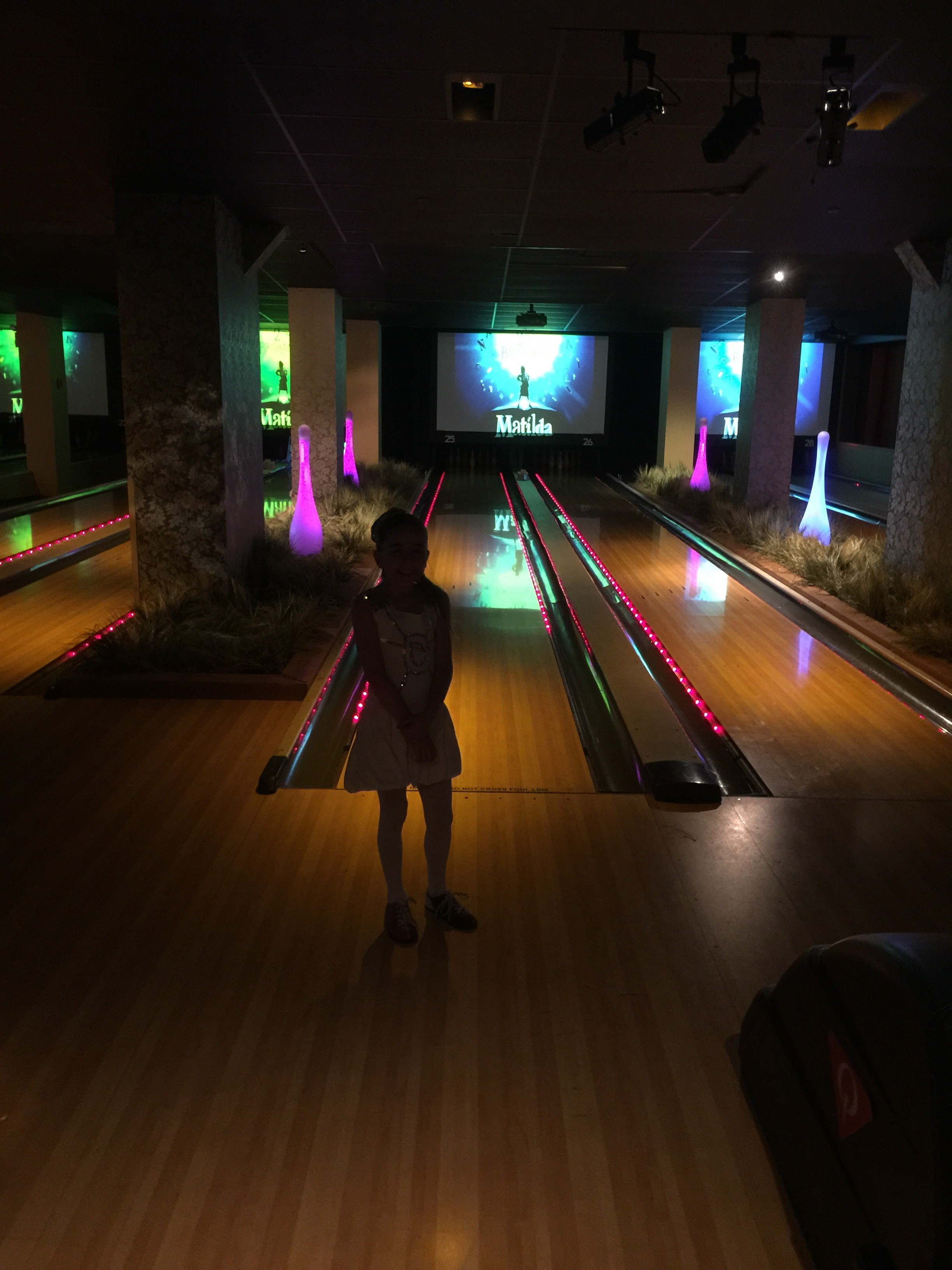 GiaNina in front of lanes at Matilda party.jpg