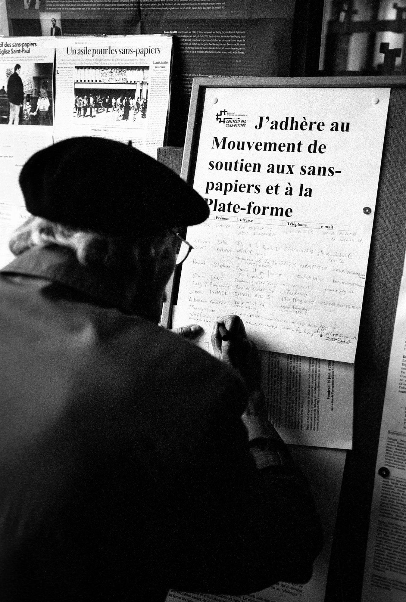 Un groupe de paroissiens de St-Paul a écrit une lettre de soutien au mouvement des sans-papiers. Le tract est distribué à la sortie d'un culte oecuménique samedi après-midi. Ici, un homme décide de signer la feuille de soutien au mouvement des sans-papiers.Fribourg, le 9 juin 2001.