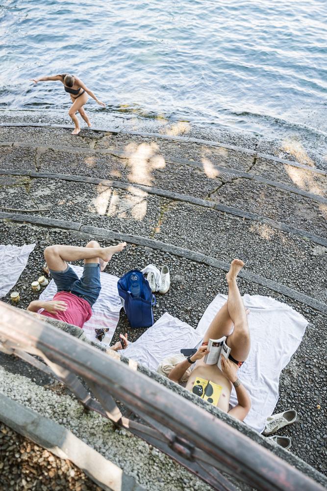 Des festivaliers en train de lire le programme du festival au bord du lac.