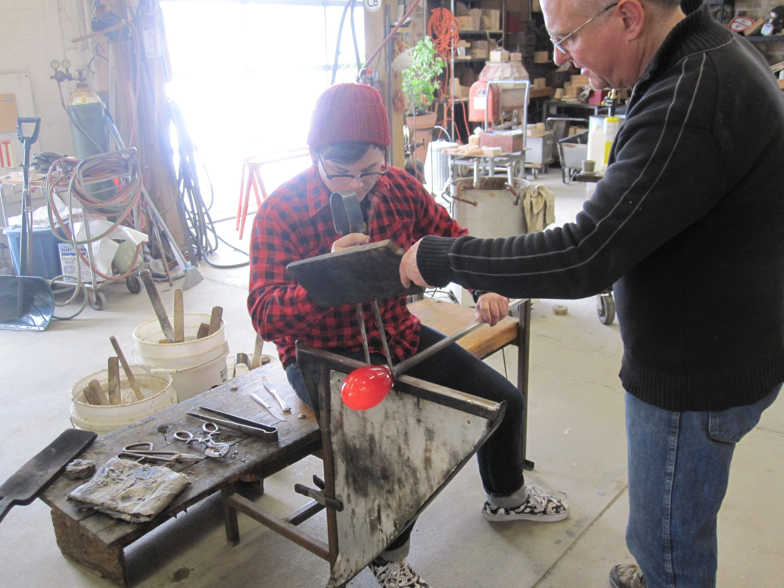 Beginner student working with hot glass.