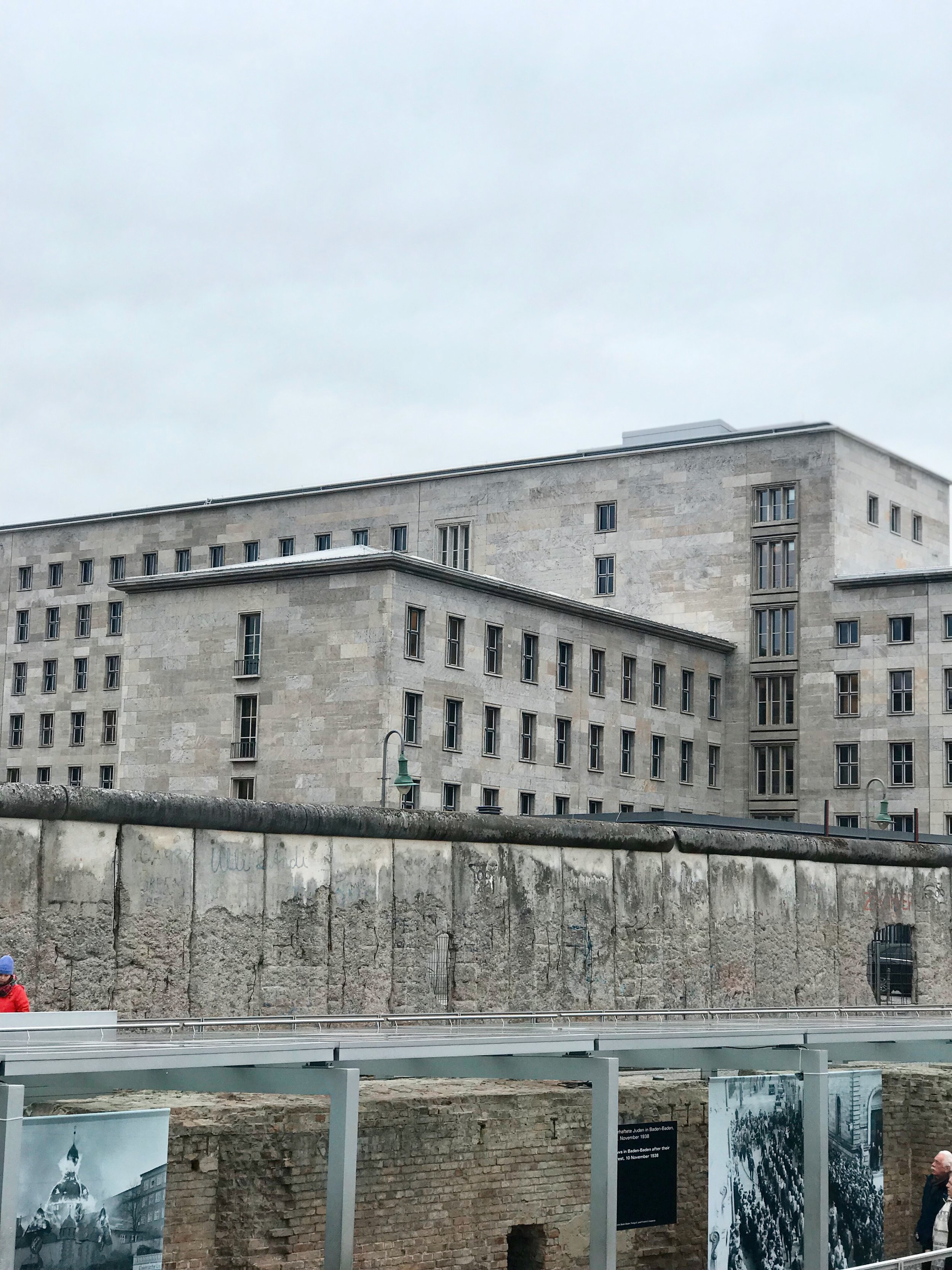 Two distinct periods in german history in one picture - Nazi building in the background, berlin wall in the fore