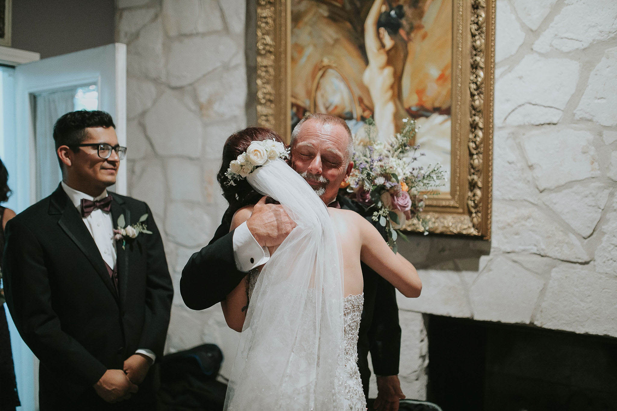 Father of the groom embraces his new daughter in law after the wedding ceremony. Shot at Casa Blanca Austin Texas by David C. Allen Photography.