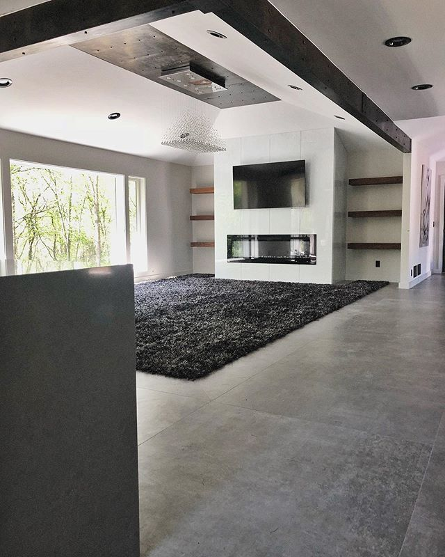 Living Room With A View ☀️ #integrity_construction_inc #contractor #builder #remodeler #renovator #livingroom #largeformattiles #minnesotatileandstone #steelbeams #glasstile #fireplace #walnut #floatingshelves #marvinintegrity #carpet #moderndesign #keepcradtalive #minnesota #twincities