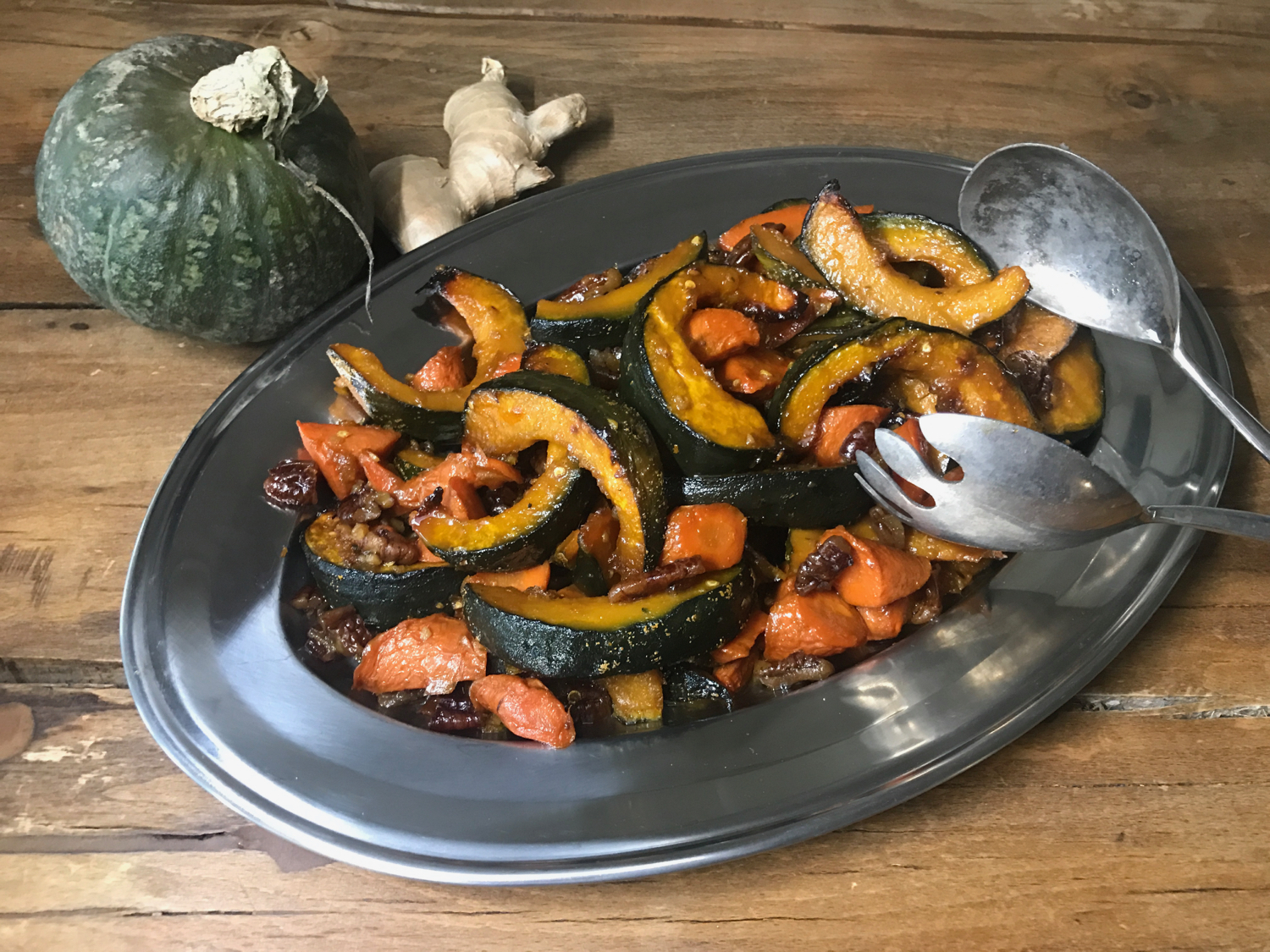 Posh Belly's Kitchen's Roasted Pumpkin and Carrots with Maple-Ginger-Thai Chili Pepper Glaze served in a stainless steel platter with vintage tongs.