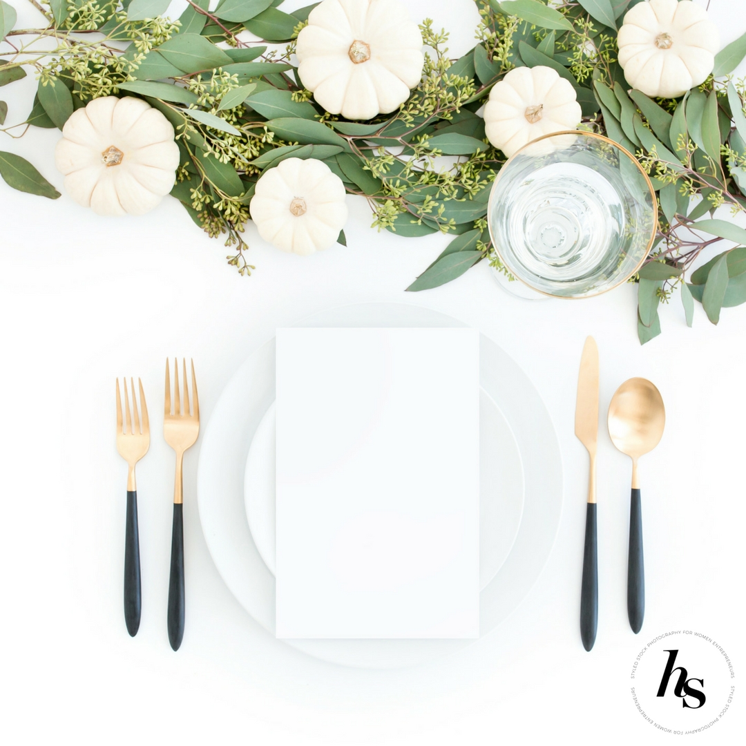 A modern, minimal Thanksgiving Tablescape styled stock invitation mockup photo from Haute Stock featuring a neutral palette of white, green, gold and black.