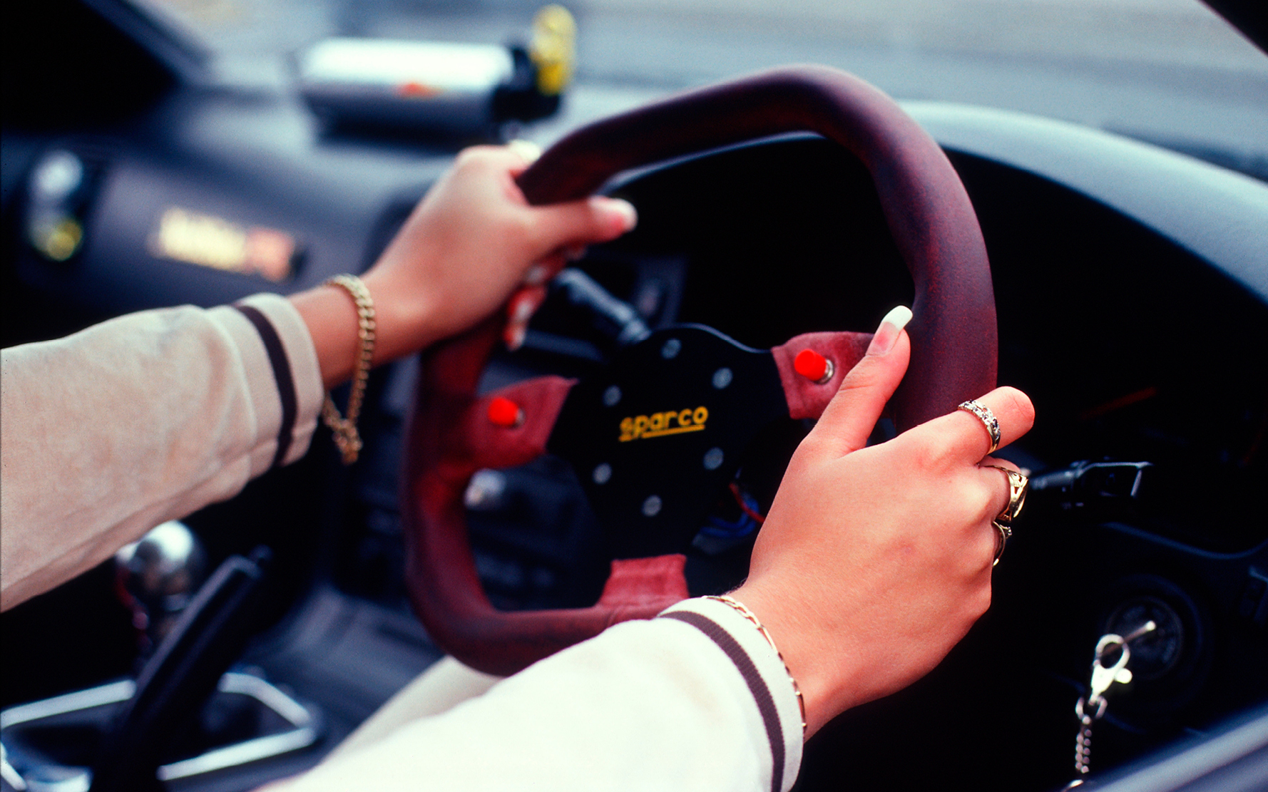 A girl with false nails, with her hands on the steering wheel of her car, Girlracers, Southend, UK 2004      ©   Naki   / PYMCA