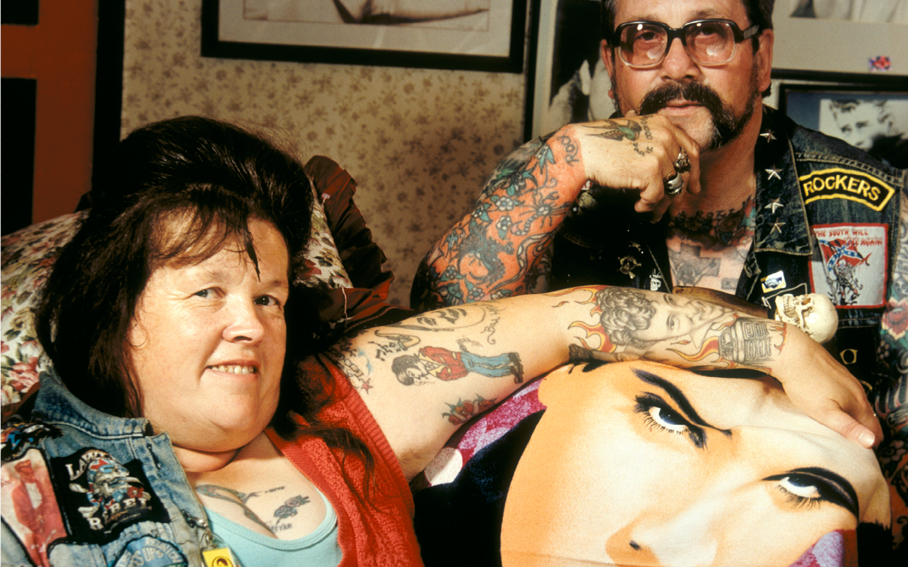 Two middle aged Elvis / Rock n' Roll fans covered with tattoos and wearing denim waistcoats with patches, posing for camera, in their home, UK 1990's  ©  David Turner  / PYMCA