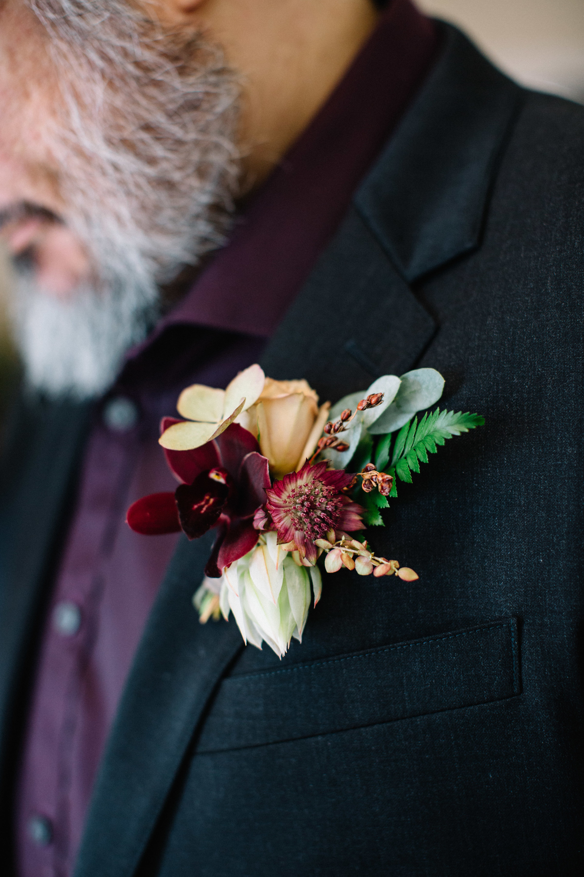 Gold and burgundy boutonnieres by Venn Floral photographed by Lucille Lawrence in Northern California at Straus Home Ranch with Mendocino Weddings.