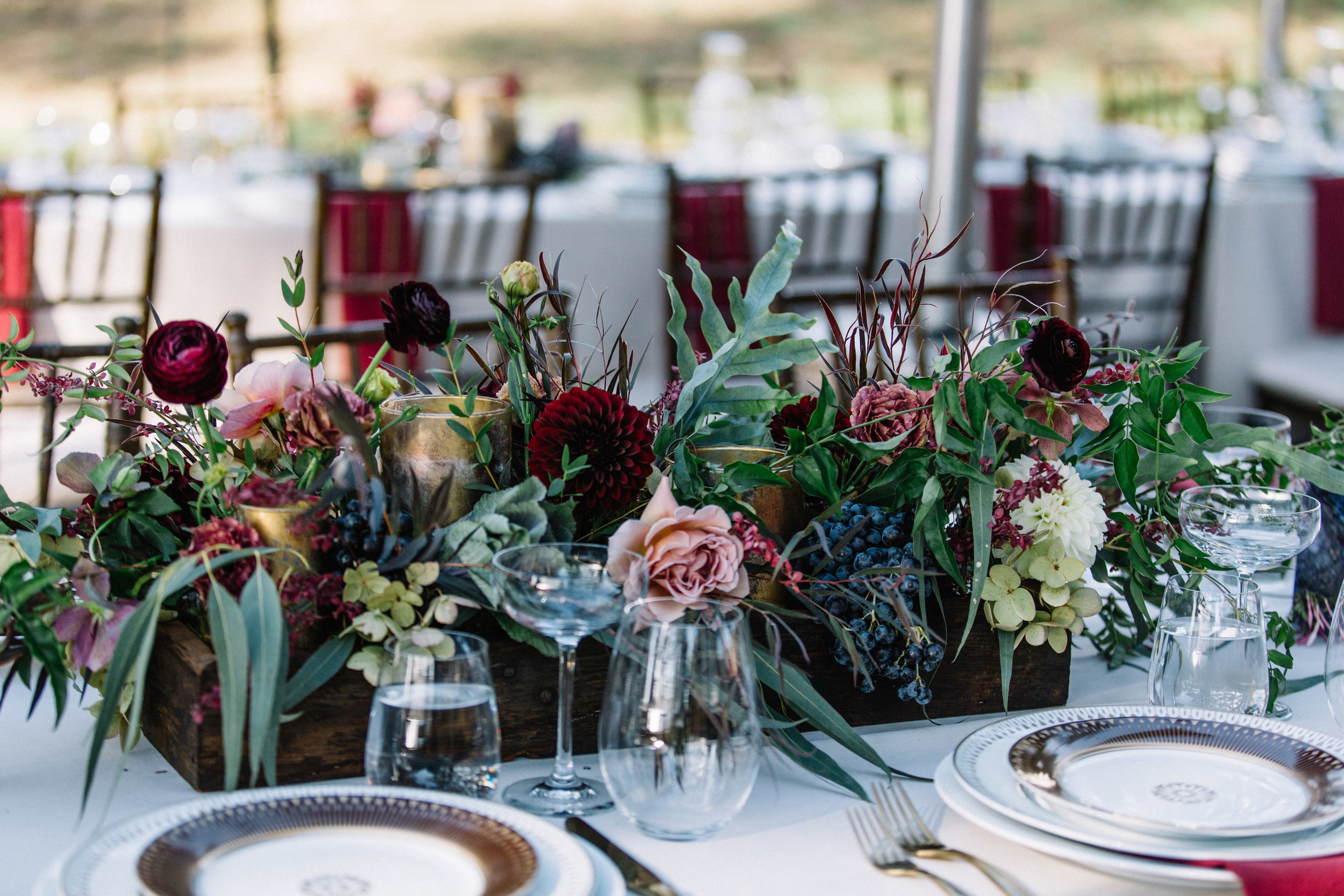 Wood box and antique gold candle centerpiece with moody florals and greenery by Venn Floral photographed by Lucille Lawrence at a coastal outdoor wedding with Mendocino Weddings, Straus Home Ranch, and Erica Steiner Fine Art.