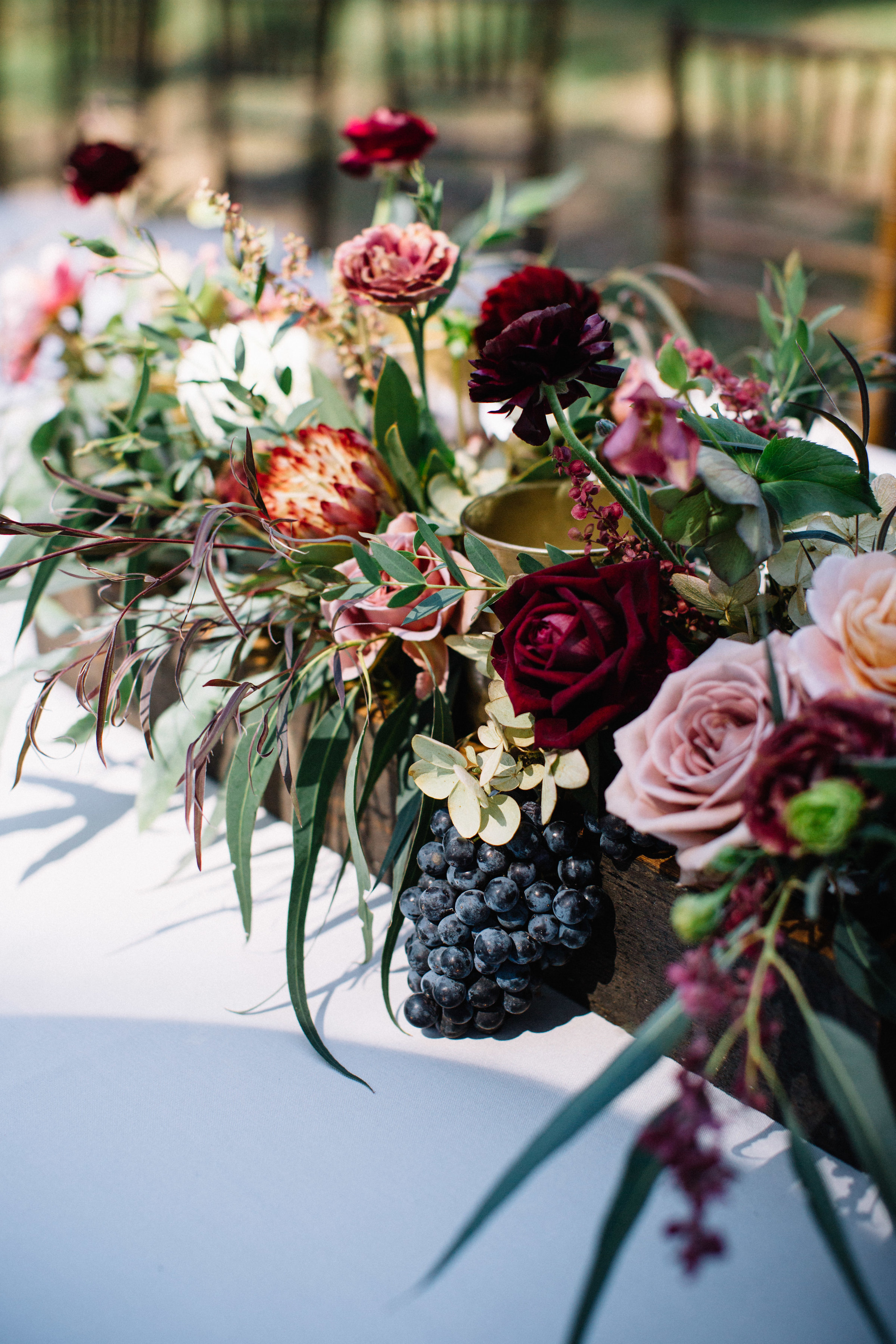 Lush centerpiece by Venn Floral with black grapes, protea, garden roses, and hellebores for an outdoor coastal wedding on Tomales Bay at Straus Home Ranch photographed by Lucille Lawrence.