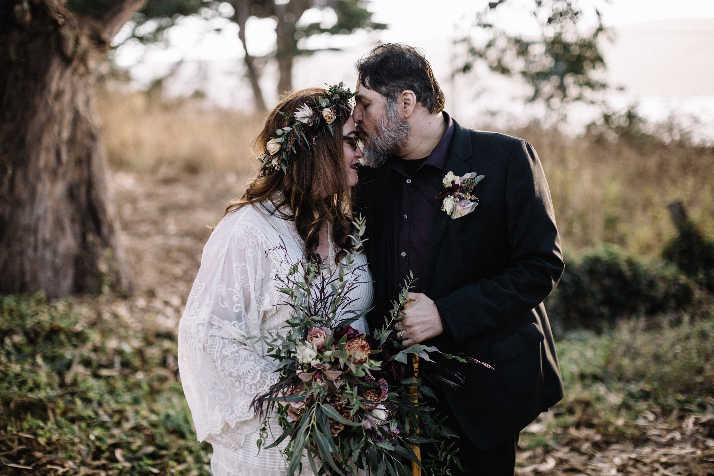 Wild bridal bouquet with soft greens and dark flowers by Venn Floral at Straus Home Ranch photographed by Lucille Lawrence.