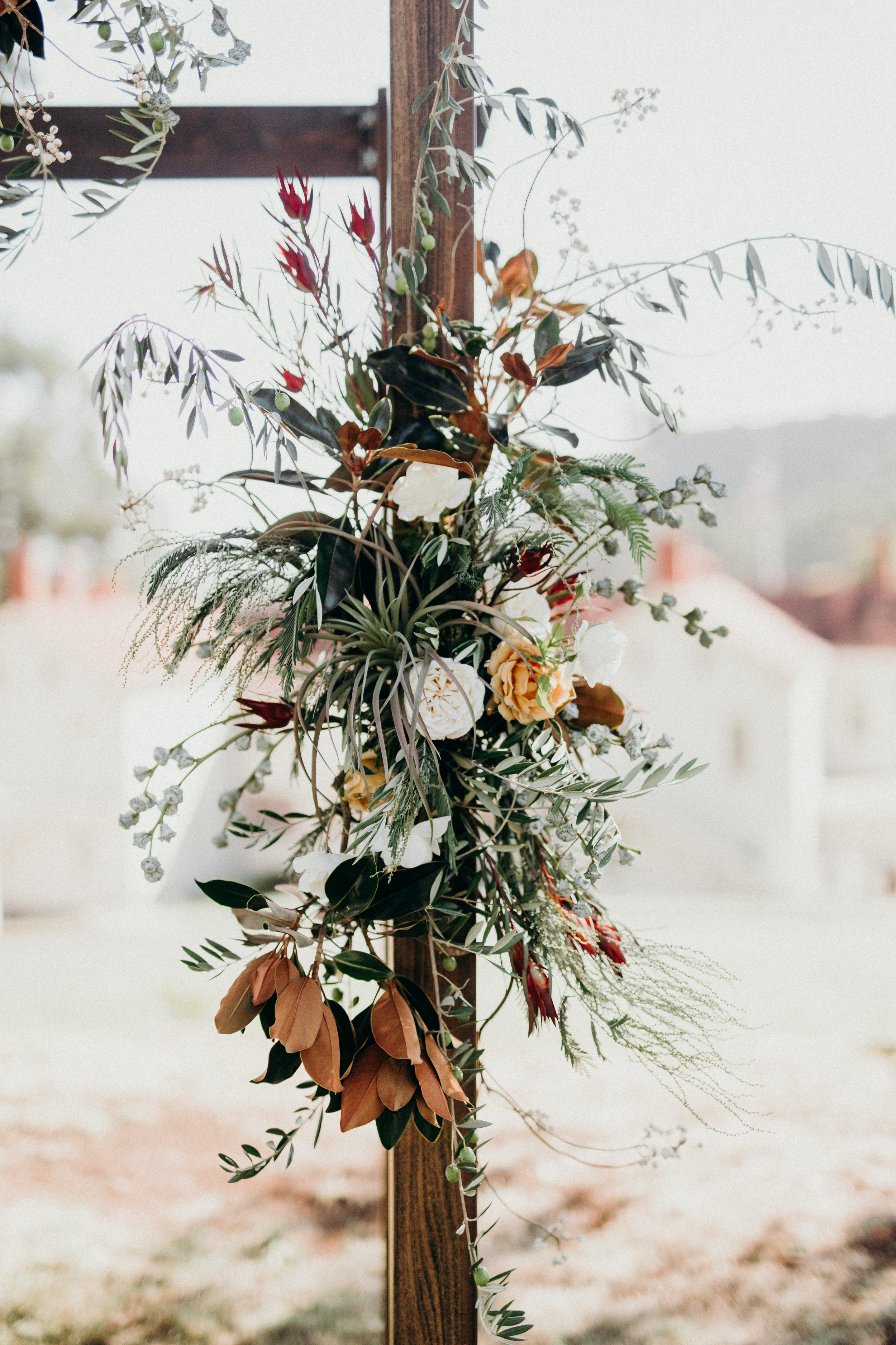 Garden inspired ceremony backdrop on wood with magnolia, olive, tillandsia and flowers by Venn Floral at Cavallo Point with Lally Events and Ryan Chard Smith Photography.