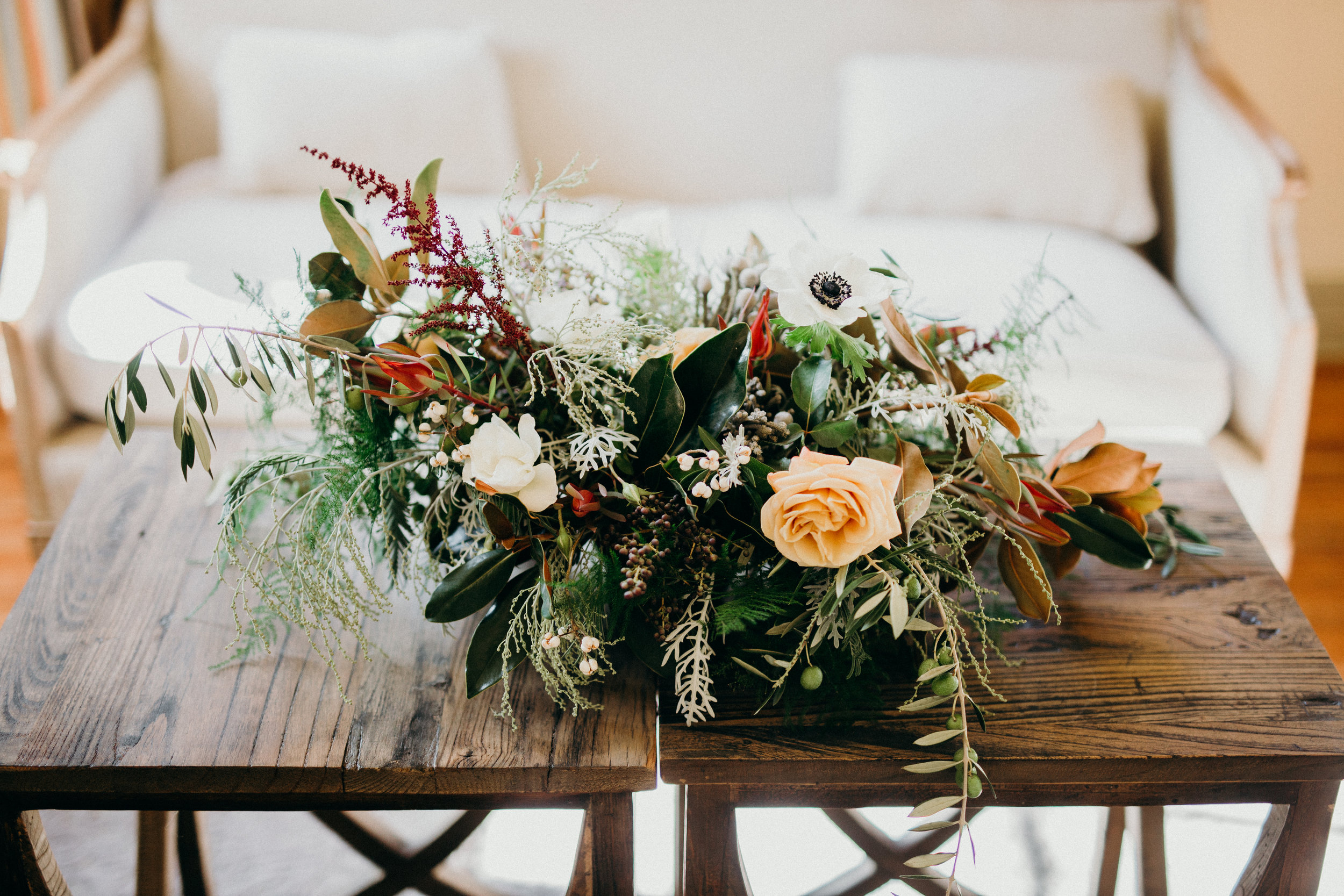 Long and low lounge arrangement in gold, white, and burgundy by Venn Floral at Cavallo Point photographed by Ryan Chard Smith,