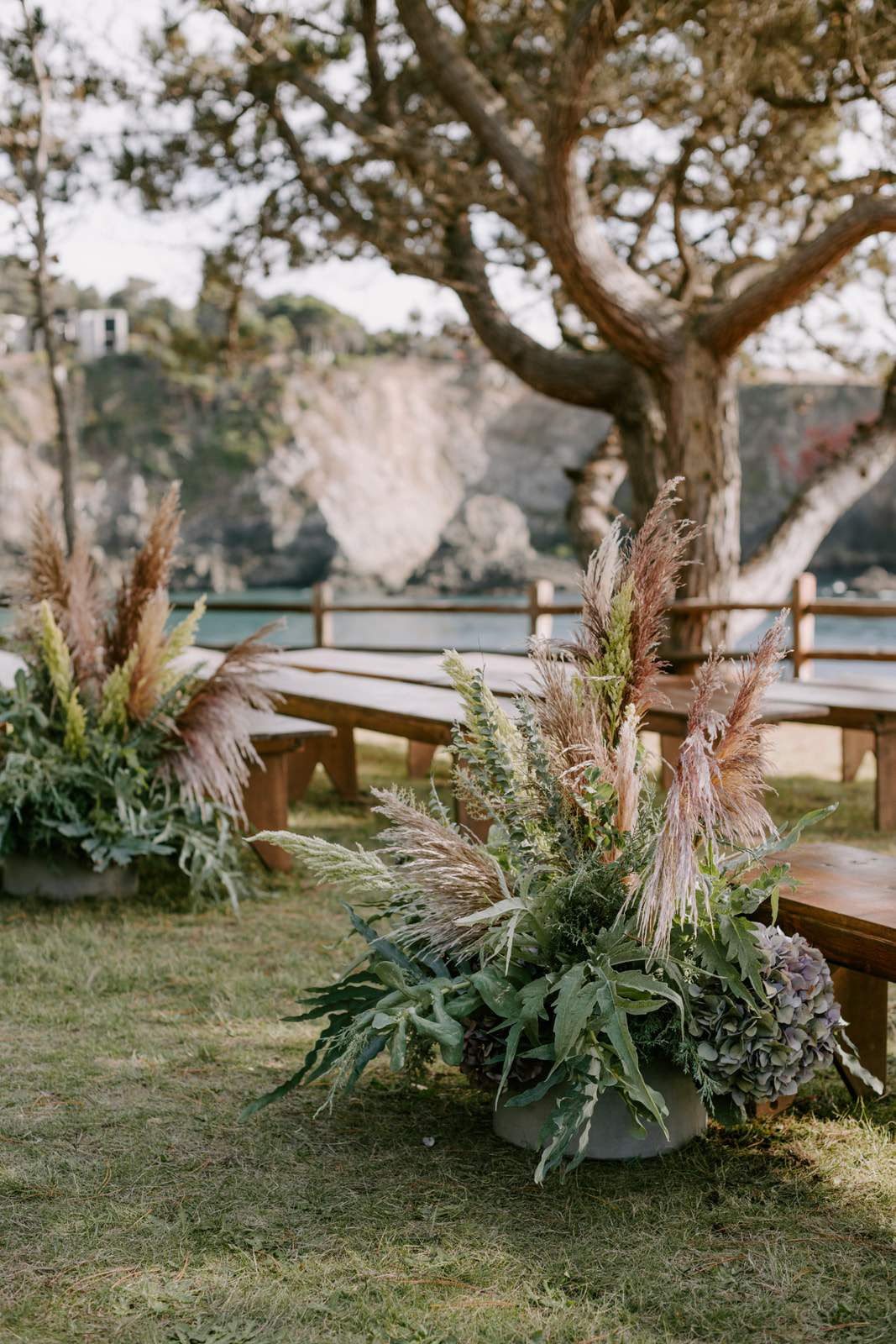 Lush aisle arrangements for a stylish oceanside wedding with fern, eucalyptus, and pampas grass by Venn Floral at Heritage House Resort photographed by Kristen Marie Parker in Mendocino.