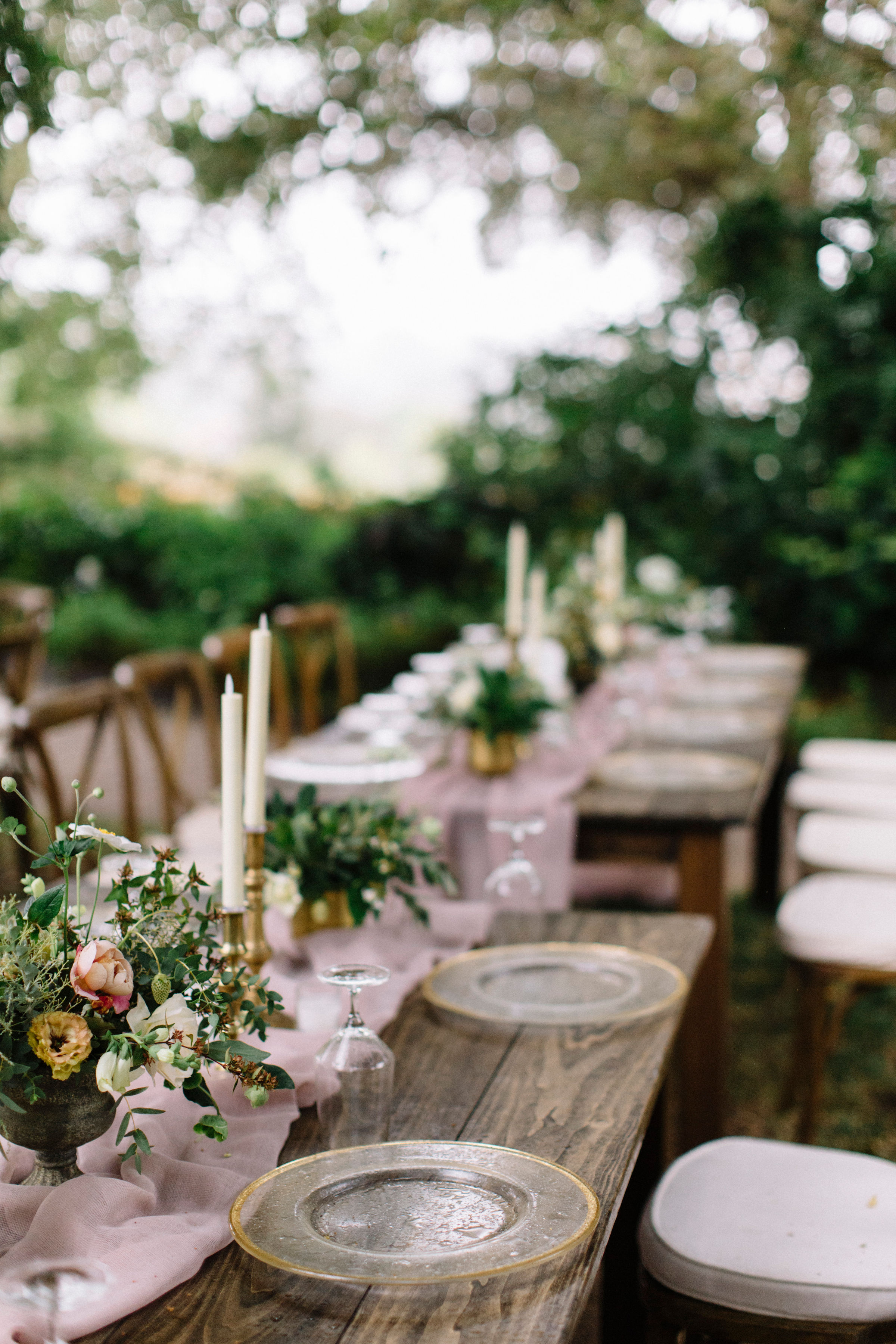 Wild and garden inspired wedding table centerpieces with taper candles and vintage glassware by Venn Floral photographed by Lucille Lawrence in Healdsburg, California.
