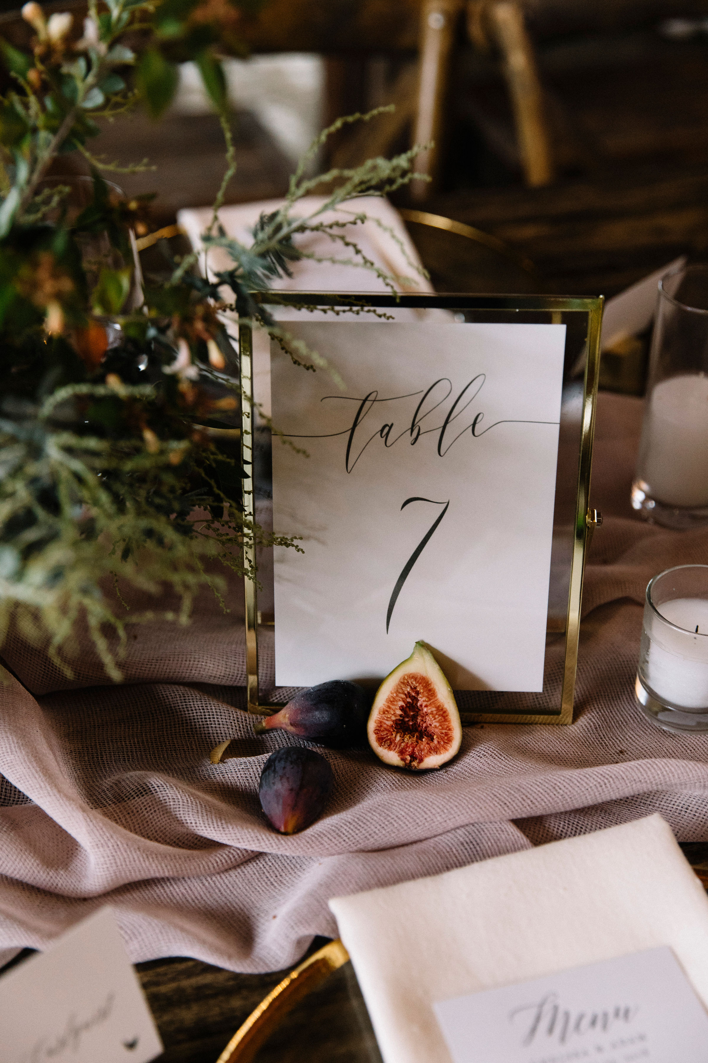 Discreet and beautiful table numbers in gold frames with cut fruit by Venn Floral photographed by Lucille Lawrence.