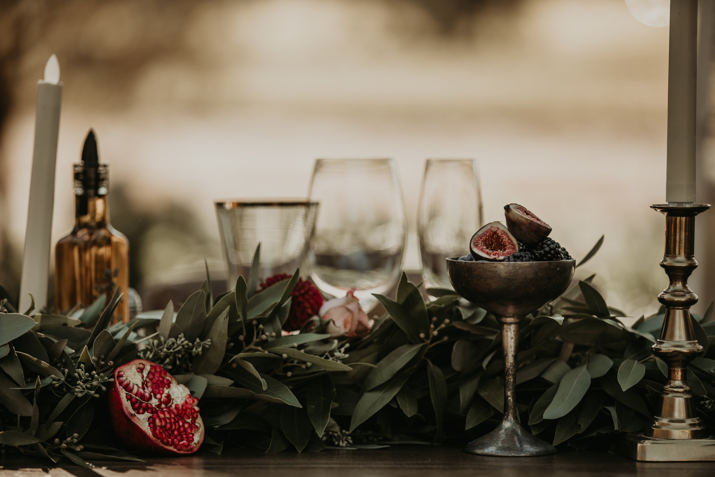 Berries, pomegranates, and greenery for a dramatic wedding tablescape by Venn Floral with Whitney Nelson Events at Beltane Ranch. Photographed by Vera Frances