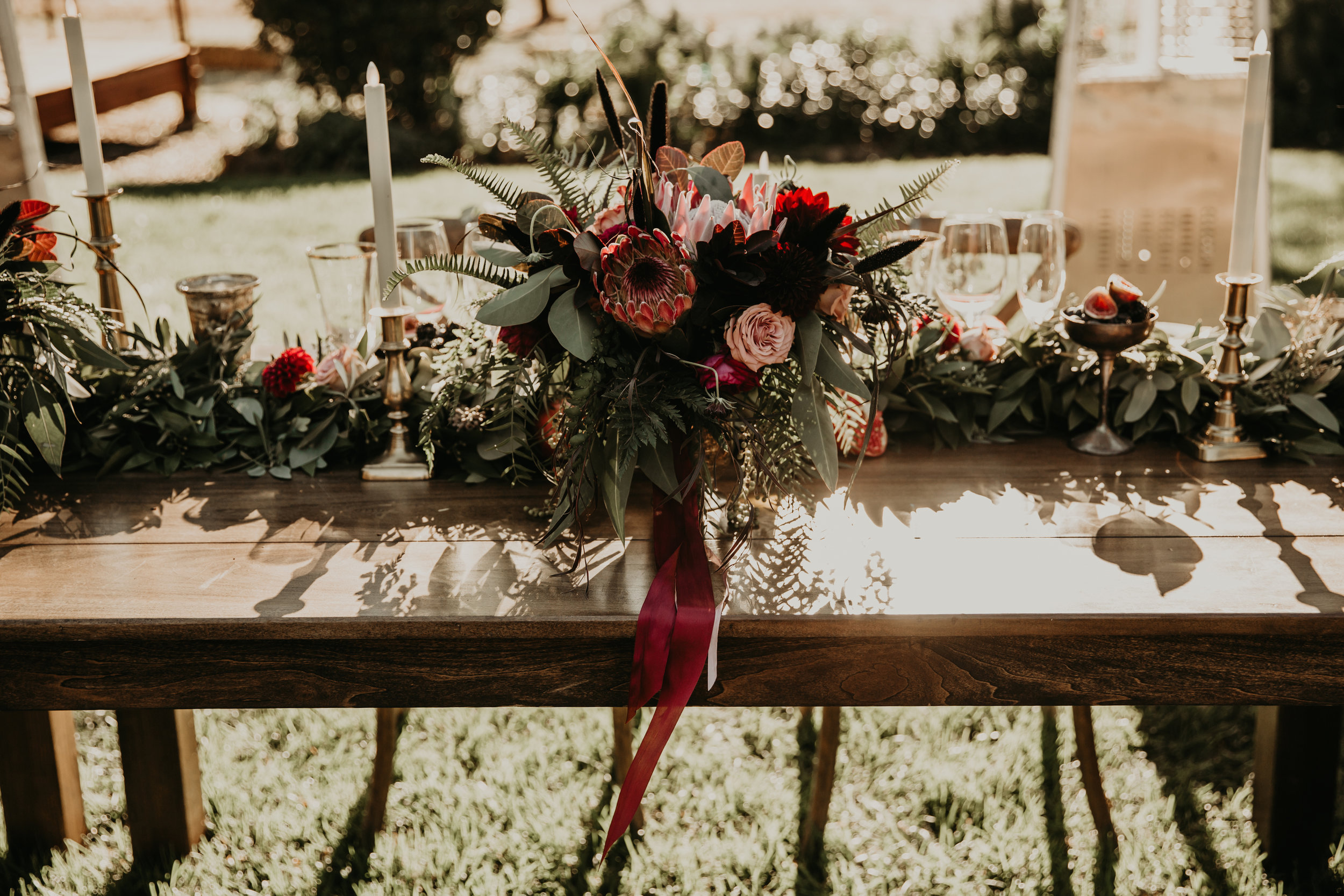 Moody flowers, cut fruit, candles, and silk ribbons for a Boho California wedding by Venn Floral with Whitney Nelson. Photographed by Vera Frances at Beltane Ranch.
