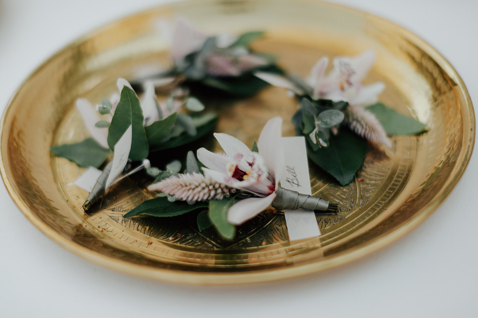 Subtle orchid boutonniere's on gold tray by Venn Floral at Ru's Farm in Healdsburg photographed by Logan Cole.