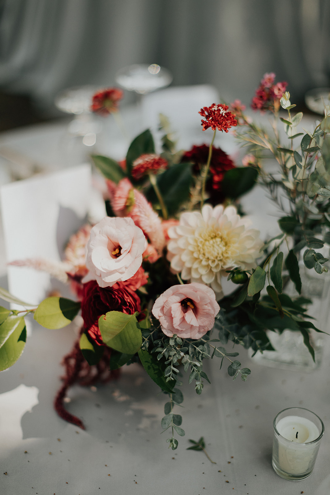 Bright summertime centerpieces with dahlias, lisianthus, roses and eucalyptus in hammered brass vases by Venn Floral at Ru's Farm in Healdsburg photographed by Logan Cole.