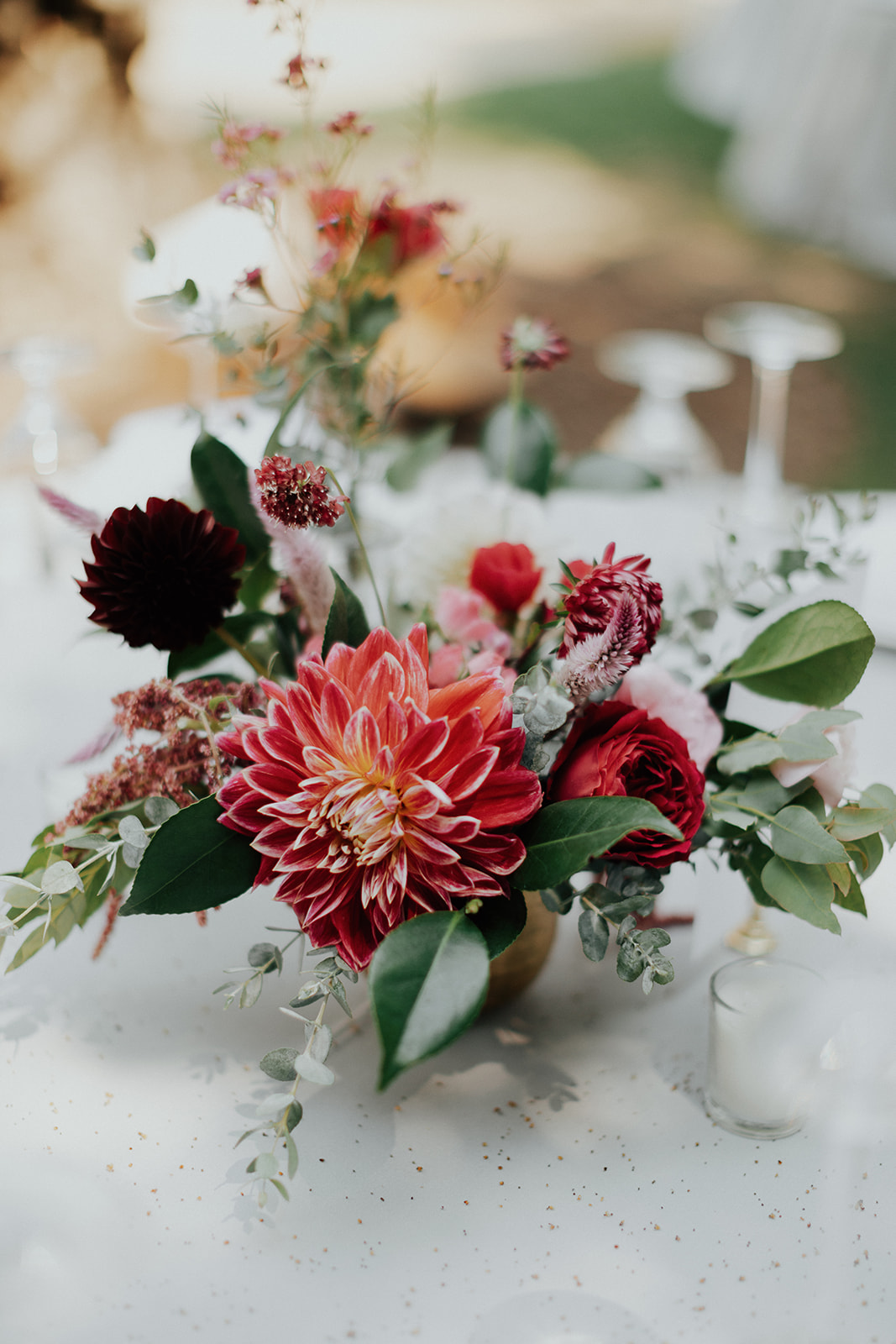 Hot pink, burgundy, blush, and coral centerpieces in gold vases. Healdsburg wedding flowers by Venn Floral at Ru's Farm photographed by Logan Cole.