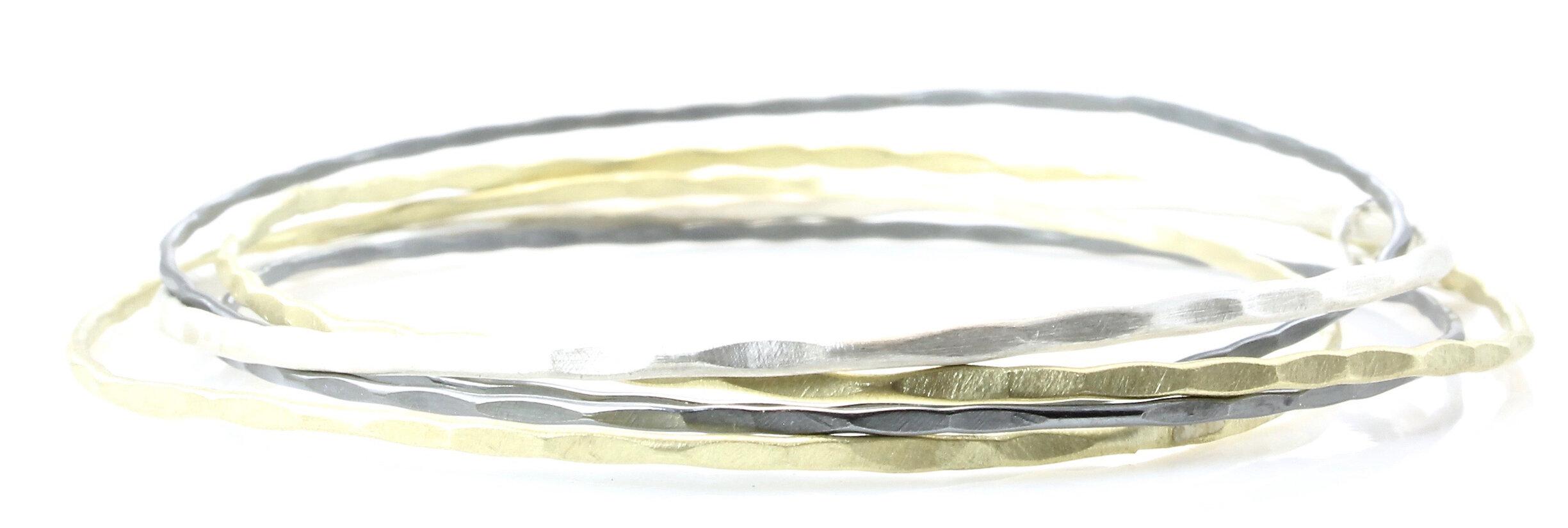 5 interlocking, hammered bangle bracelets in 18k gold, sterling silver and oxidized sterling silver