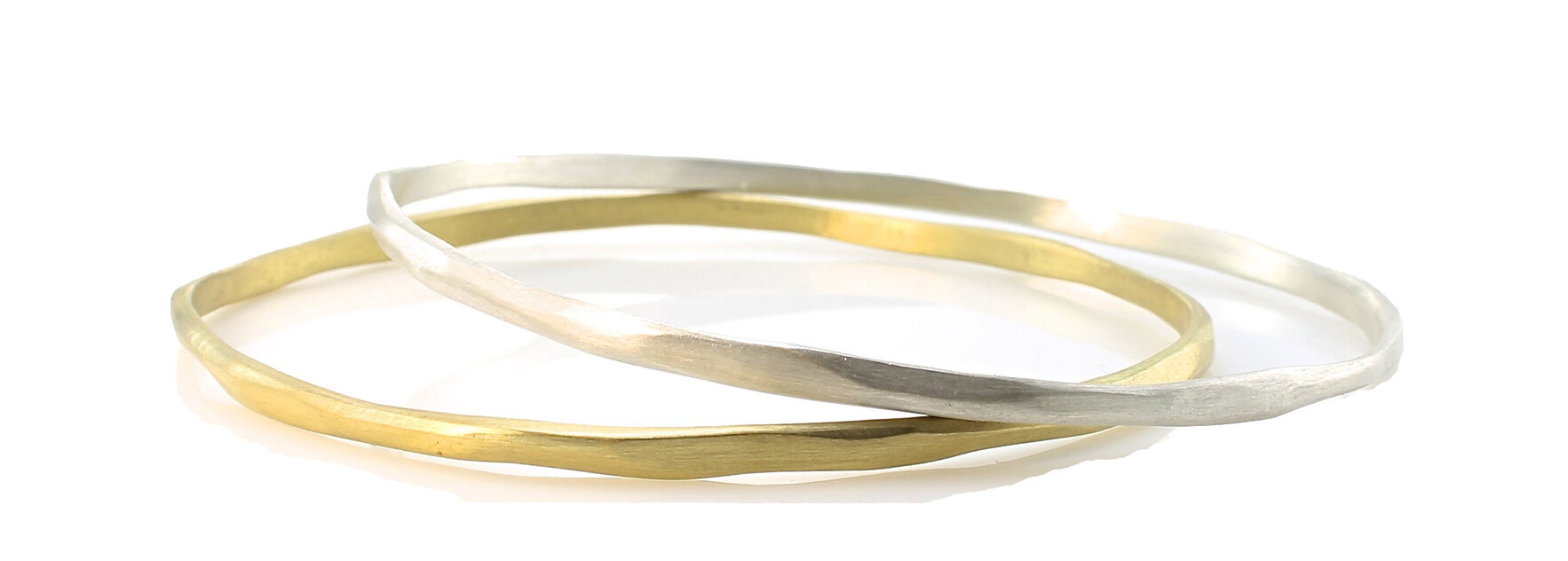 Thin, carved bangles in 18k gold and sterling silver