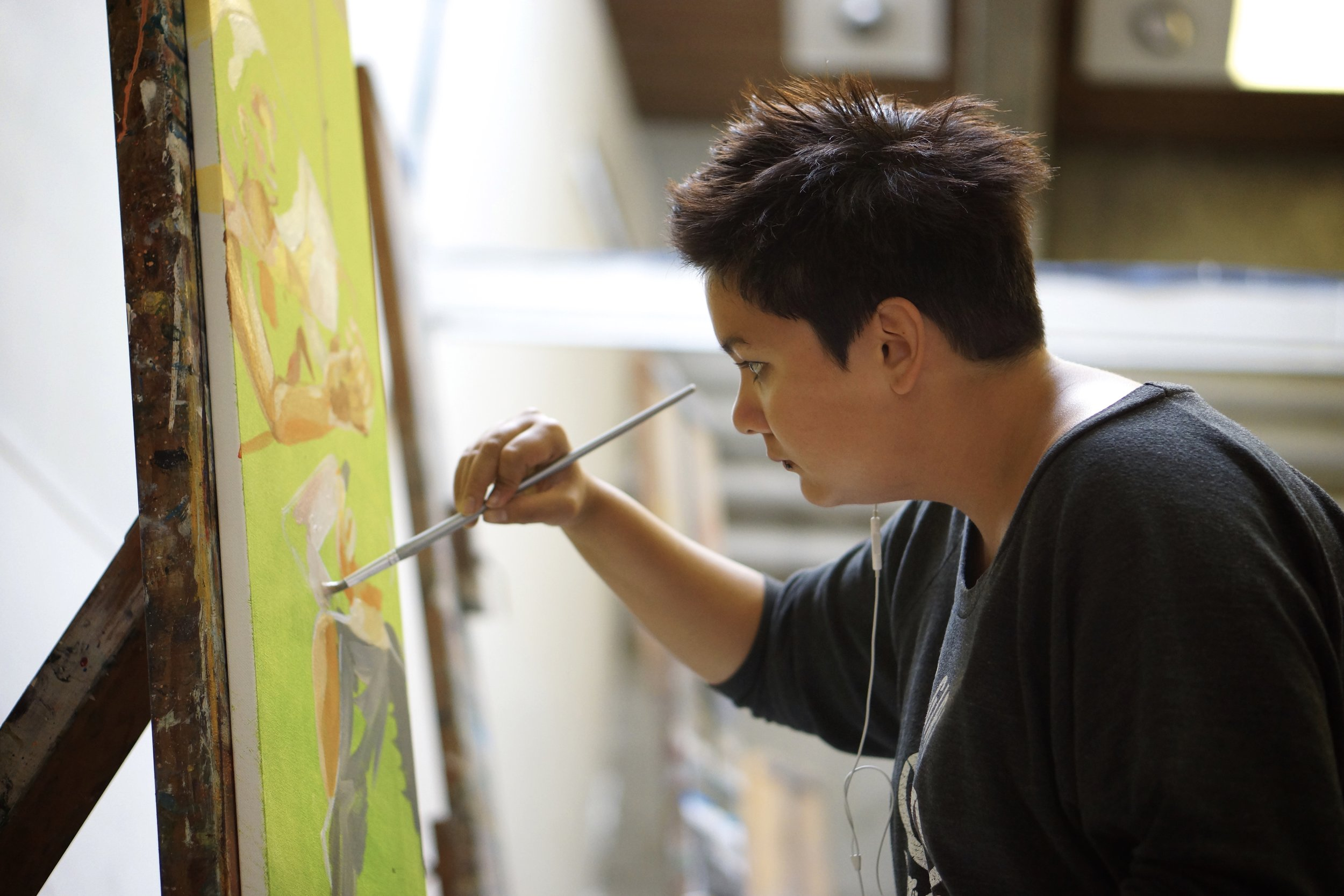 "Althea Solis, a senior Art Practice major, works on a final painting. ""For the most part,"" she says, ""I've been focusing on the relationship between the Philippines and America. Now I'm moving into new symbols, science fiction imagery, because I'be been working in science fiction outside of painting, in comics."" This painting is a part of a series she calls, ""The Loneliness Series."""