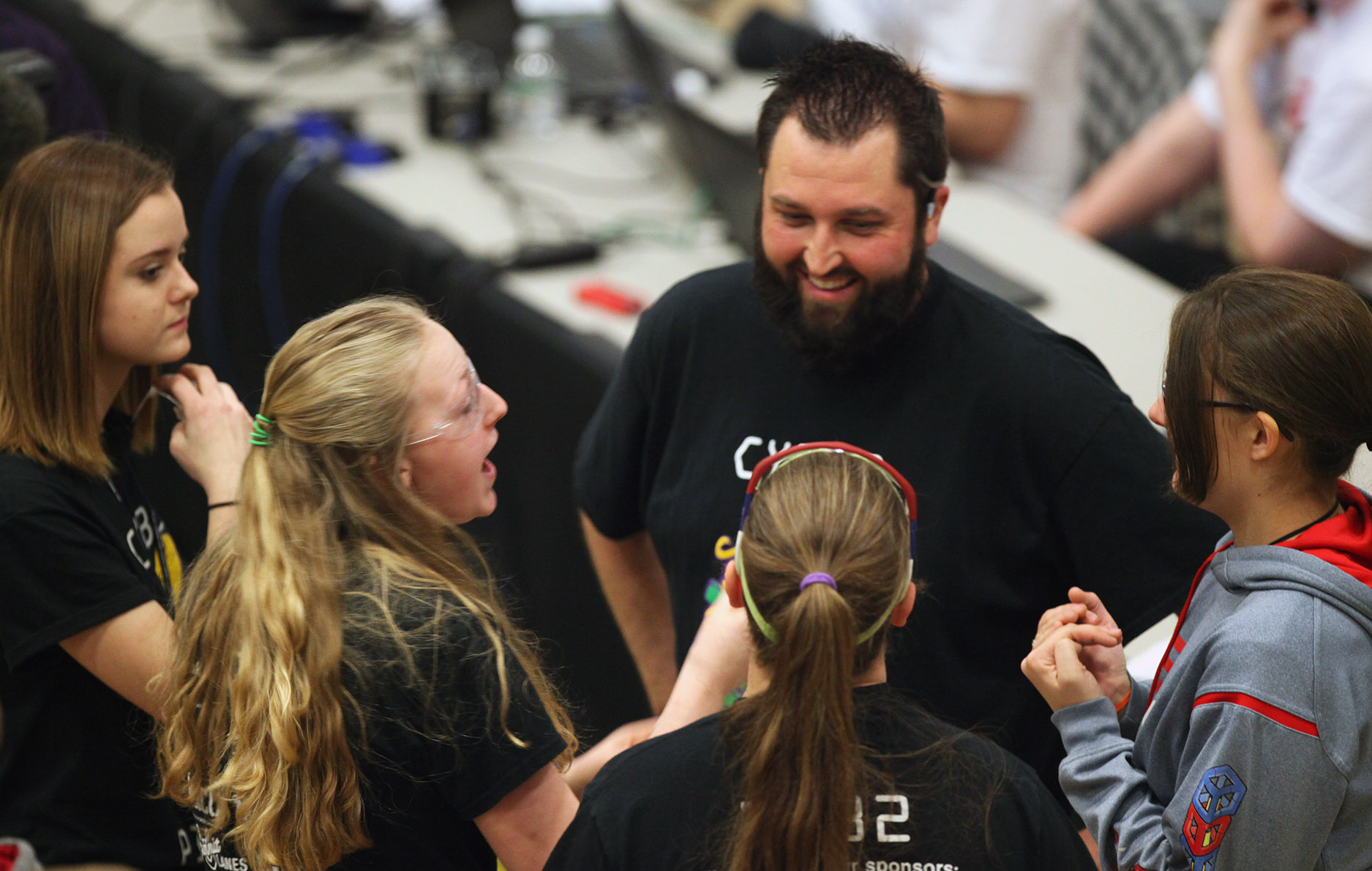 From left, Hannah Engler, 15, Kaitlyn De Kan, 17, Allie Floyd, 18, and Shannon Coupland, 17, talk with their coach, Adam Arnold, during the VEX Missouri State Robotics Championship in Rolla on Saturday. The team won three awards based on their performance throughout the day.