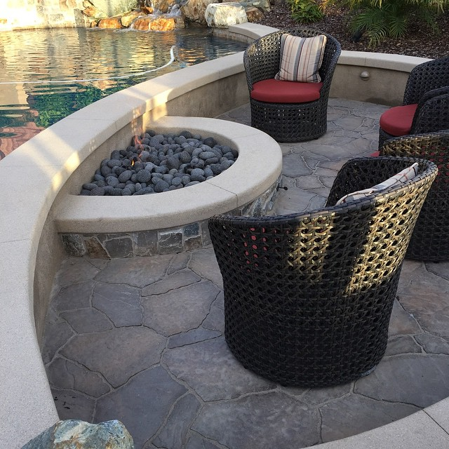 Sunken fire pit with natural rock waterfall.