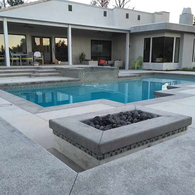 Tumbled lava rock in a modern mix of gray tones. Pewter gray cantilever concrete with Outback gray topcast concrete decking. Mid tone gray plaster pool.