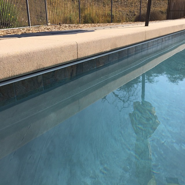 Automatic pool cover track system under cantilever concrete. Gray plaster