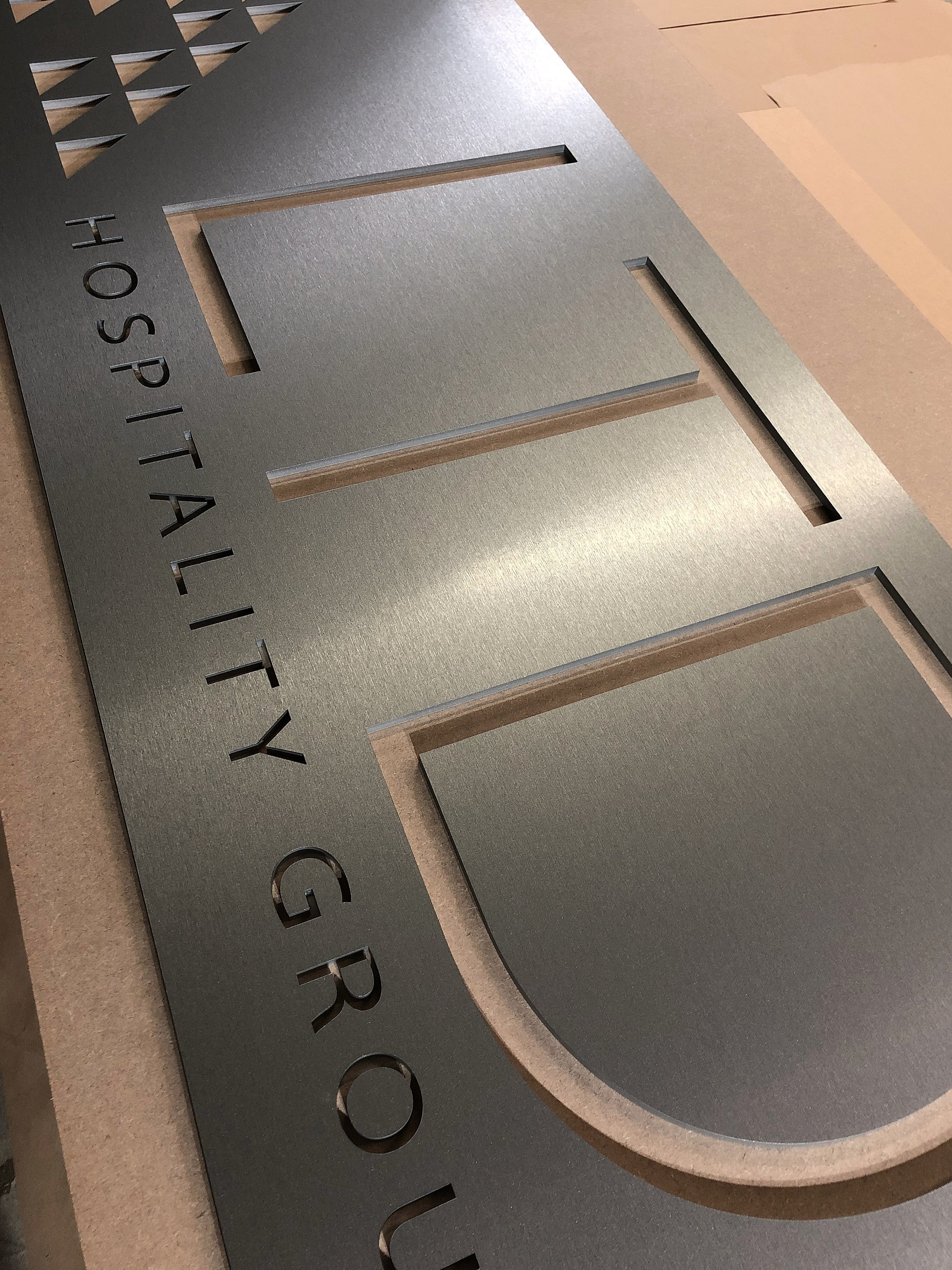 Laser cut office sign with brushed titanium finish.