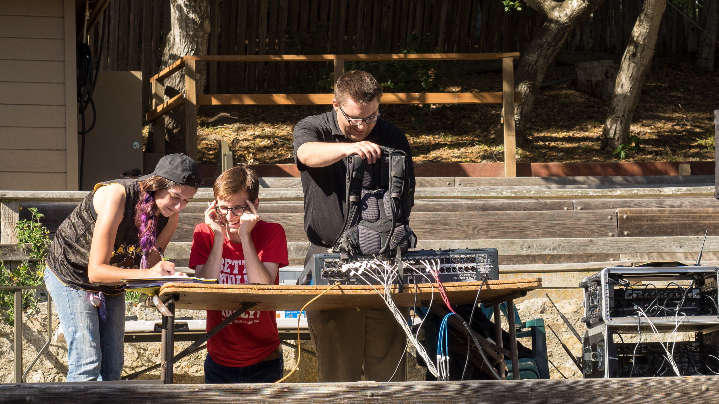 (Left to Right) Sierra Luna Gibson, Jerrod Uniwtiz, and Andrew Folk excitedly prepare the sound equipment for Pippin's Preview Performance.