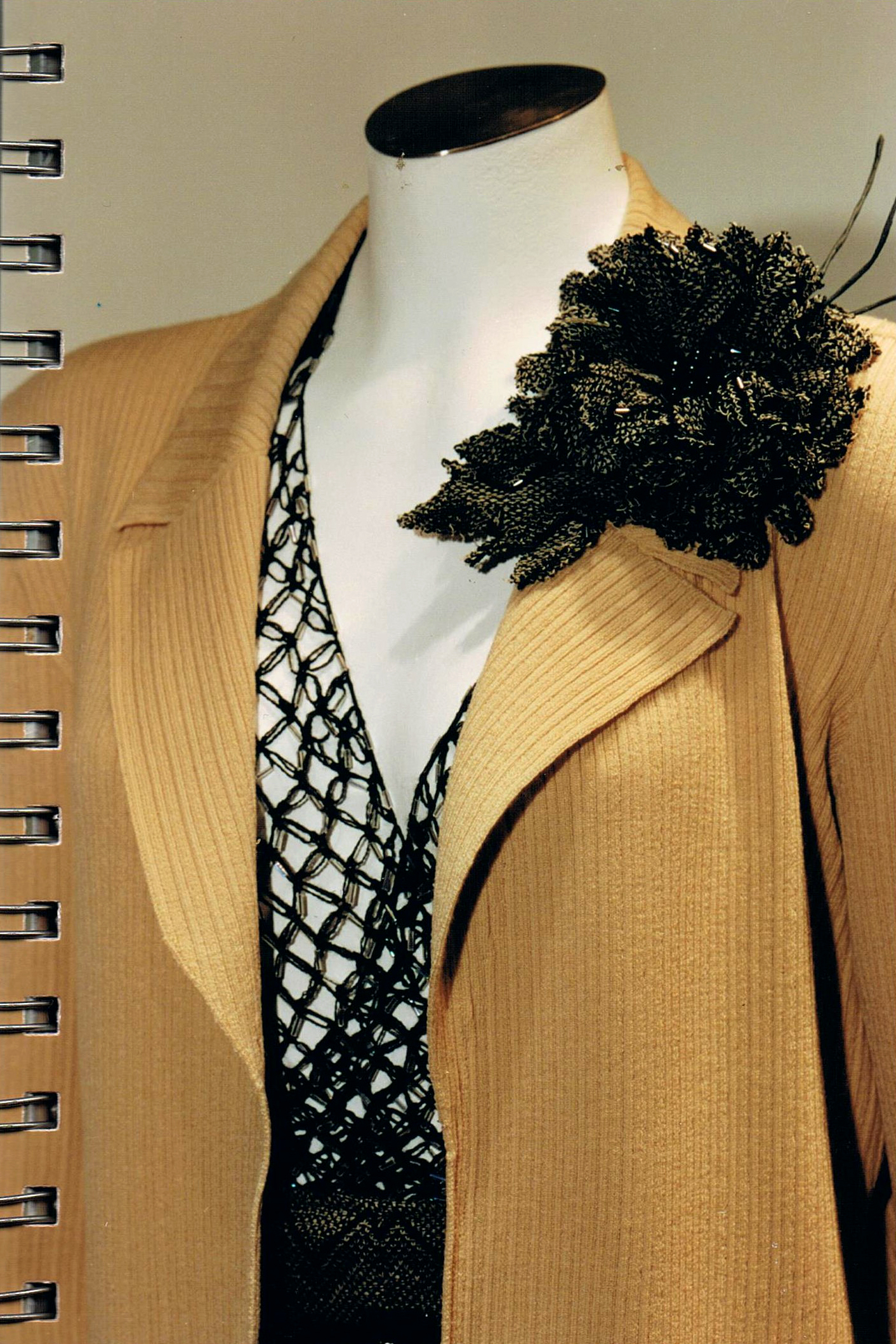 """Dettaglio di blazer e top incrociato a """"punto strega"""" all'uncinetto."""