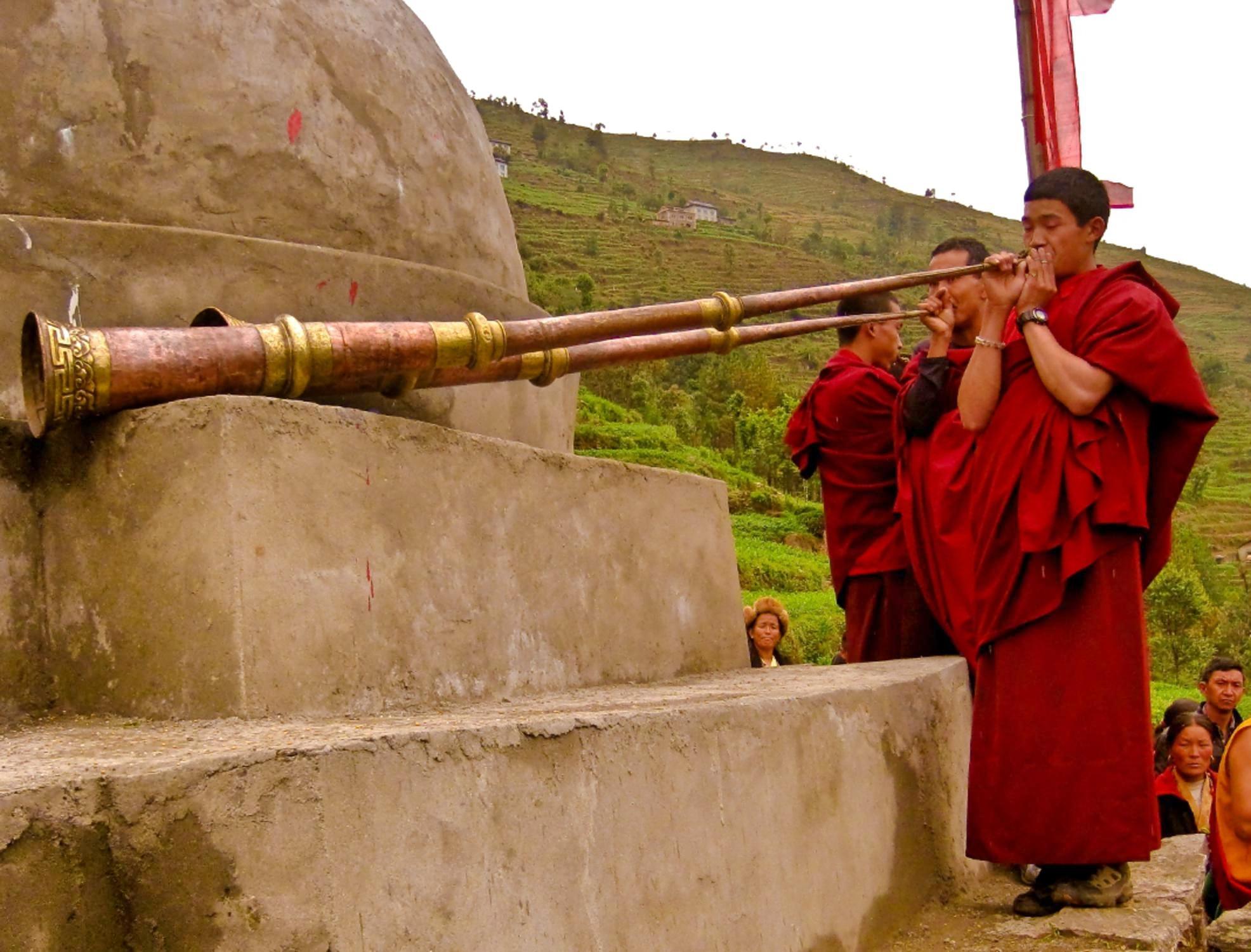 Buddhist monks blow traditional dungchen dharma trumpet horns in Bumburi village Solu Khumbu Nepal