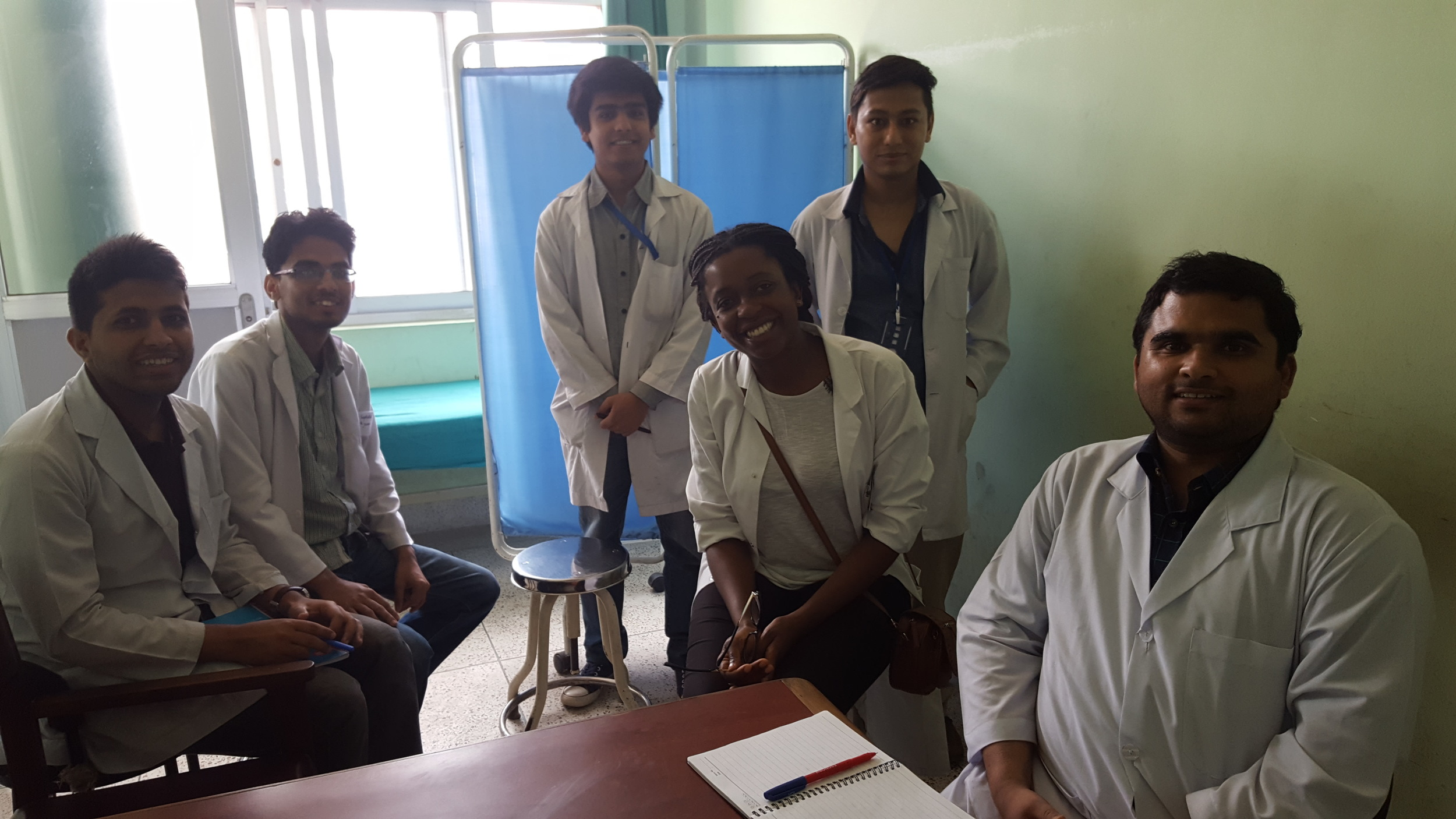 medical elective students surrounded by her supervisor.