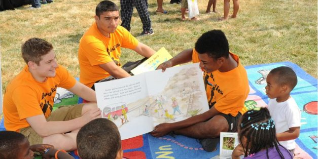 (L-R) Zane Kruszynski, Rudy Vasquez and Jason Johnson share a book with young kids at the Weiler Homes.